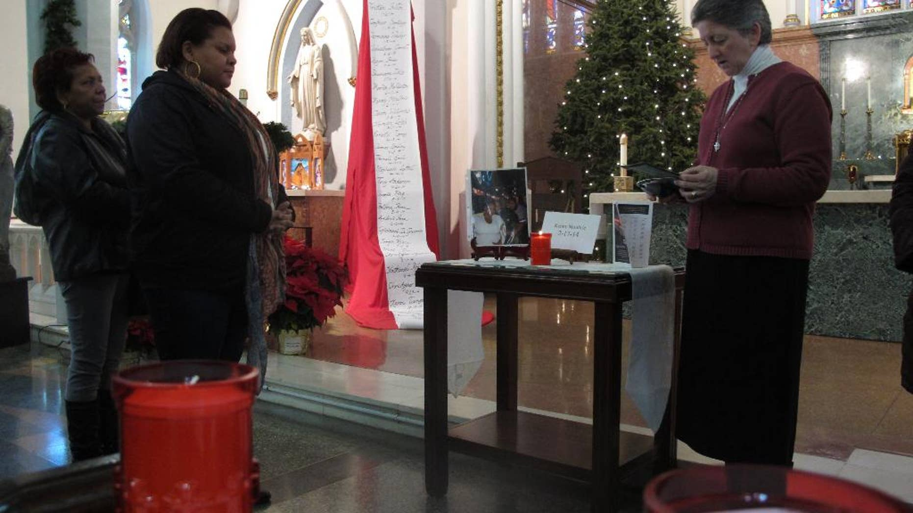 In this Tuesday, Dec. 30, 2014 photo, Carmen Marquez watches as Sister Helen Cole leads a vigil for the 32 murder victims in 2014, at Cathedral of the Immaculate Conception in Camden, N.J. Marquez's husband, Kenny Moultrie, was among the victims who were being remembered. (AP Photo/Geoff Mulvihill)