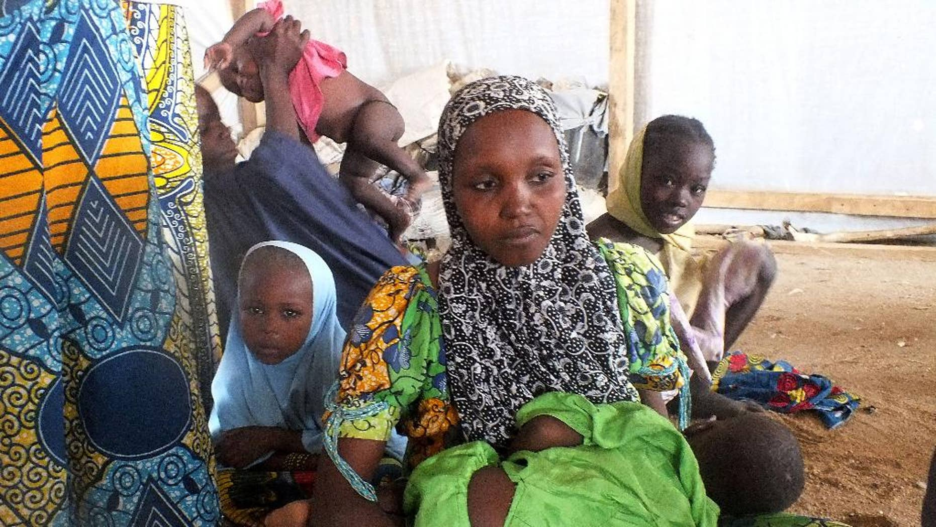 FILE -In this file photo taken on Wednesday, Feb. 25, 2015, a family of refugees that fled their homes due to violence from the Islamic extremist group Boko Haram sit inside a refugee camp in Minawao, Cameroon. With radical Islamic insurgents on its doorstep, Cameroon is trying to head off unrest at home by quelling any signs of the extremism that has roiled neighboring Nigeria. In recent months, Cameroon has arrested dozens of imams and their followers accused of promoting radical ideology and collaborating with Nigeria's Boko Haram militants. (AP Photo/Edwin Kindzeka Moki)