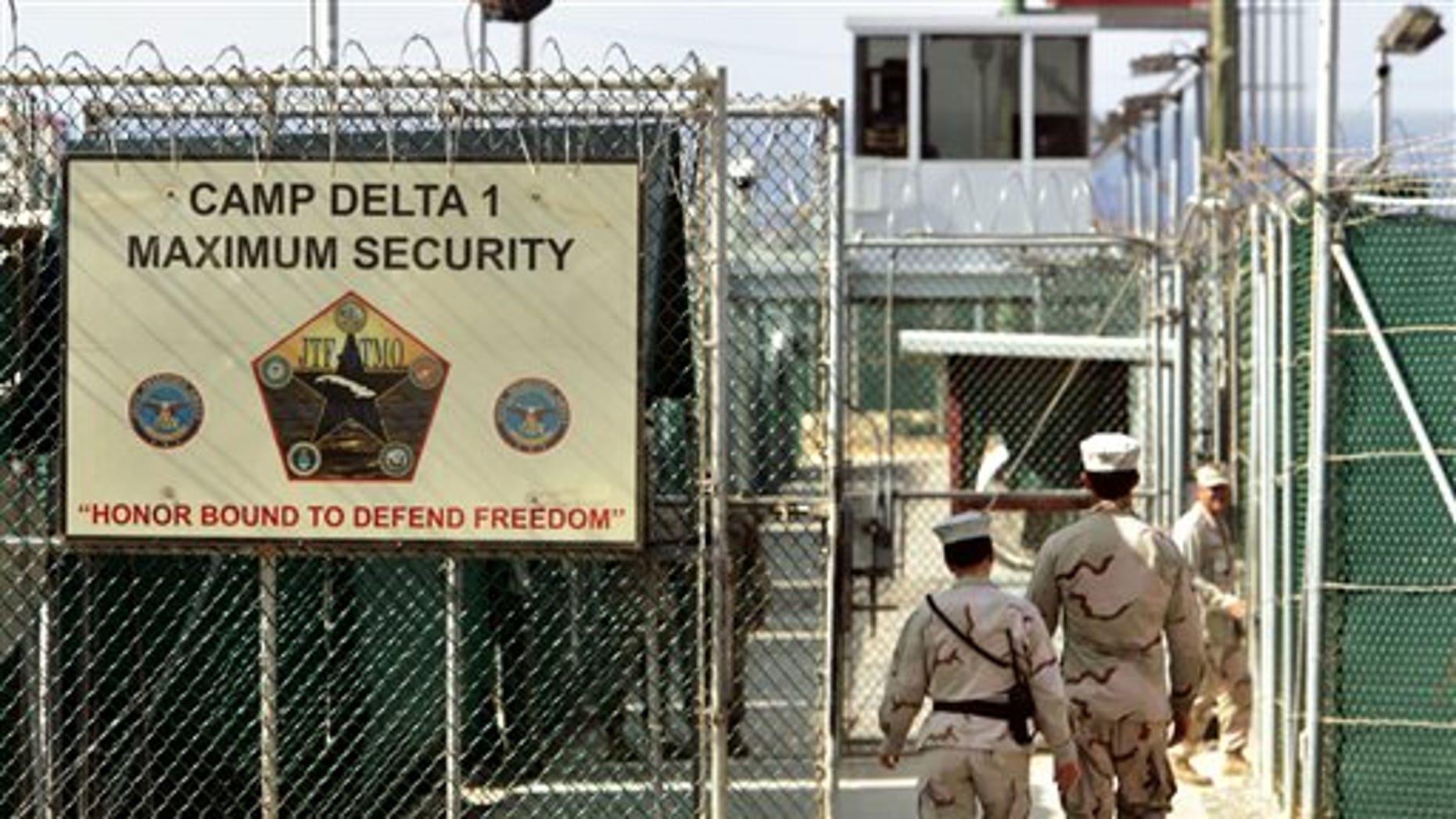 U.S. military guards walk within Camp Delta military-run prison, at the Guantanamo Bay U.S. Naval Base, Cuba.
