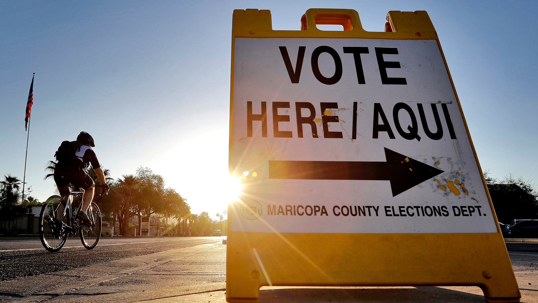 FILE - In this Aug. 30, 2016 file photo, a cyclist rides past a sign directing voters to a primary election voting station early, in Phoenix. Early voting kicks off next week in North Carolina, the first in a two-month run of voting through key swing states where non-whites and young adults could give one of the presidential campaigns a decisive advantage before Election Day.   (AP Photo/Matt York, File)