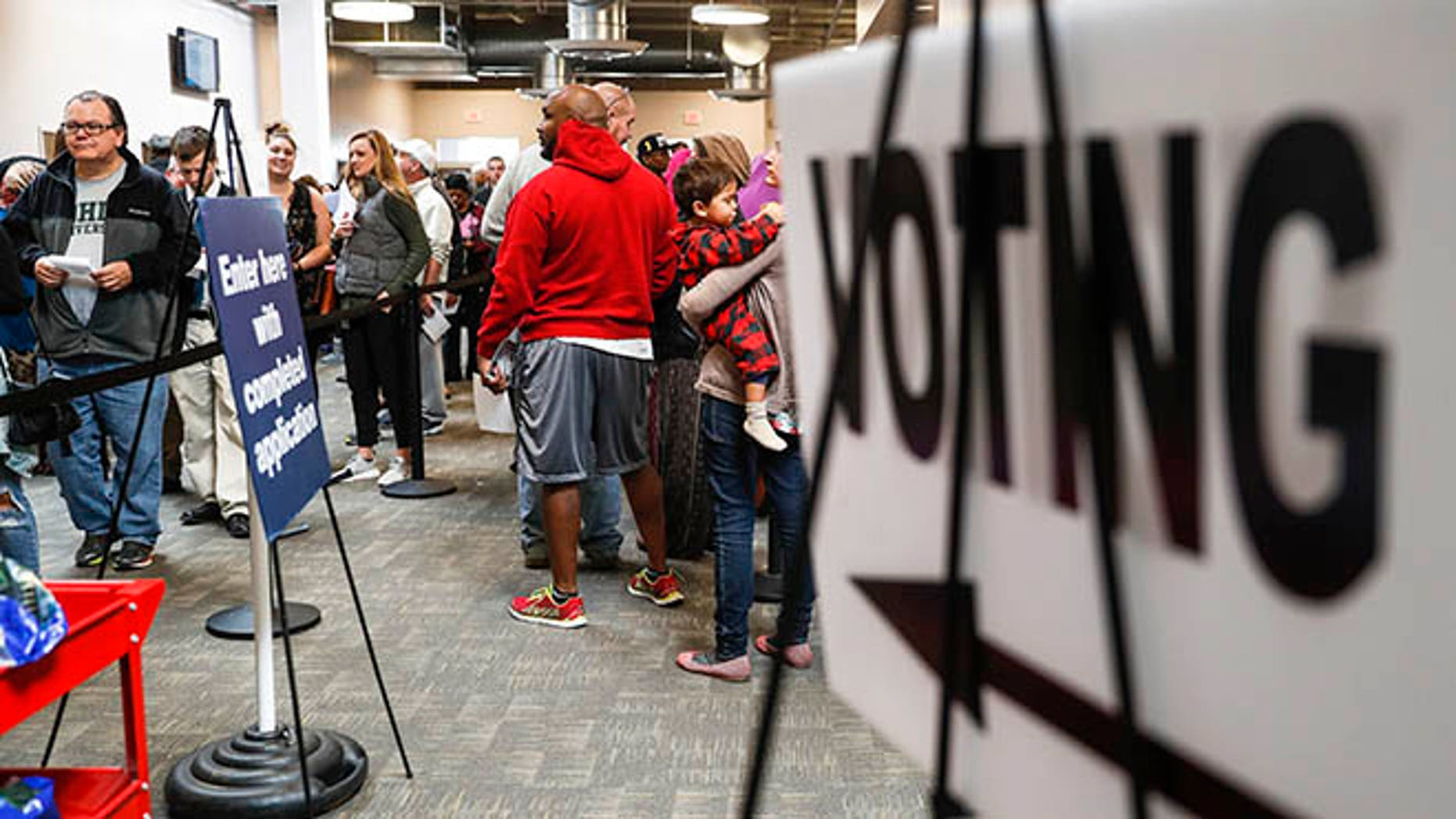 A line of early voters wait in queue at the Franklin County Board of Elections, Monday, Nov. 7, 2016, in Columbus, Ohio. Heavy turnout has caused long lines as voters take advantage of their last opportunity to vote before election day. (AP Photo/John Minchillo)