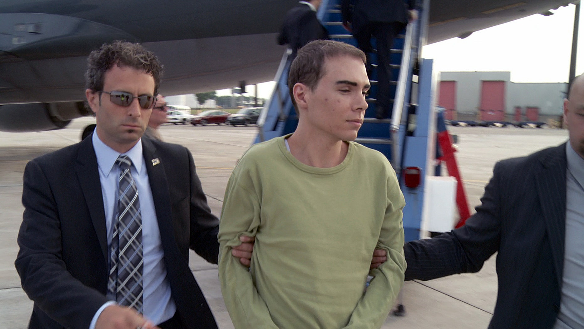June 18, 2012: In this photo provided by Montreal Police, Luka Rocco Magnotta is taken by police from a Canadian military plane to a waiting van on Monday in Mirabel, Quebec.