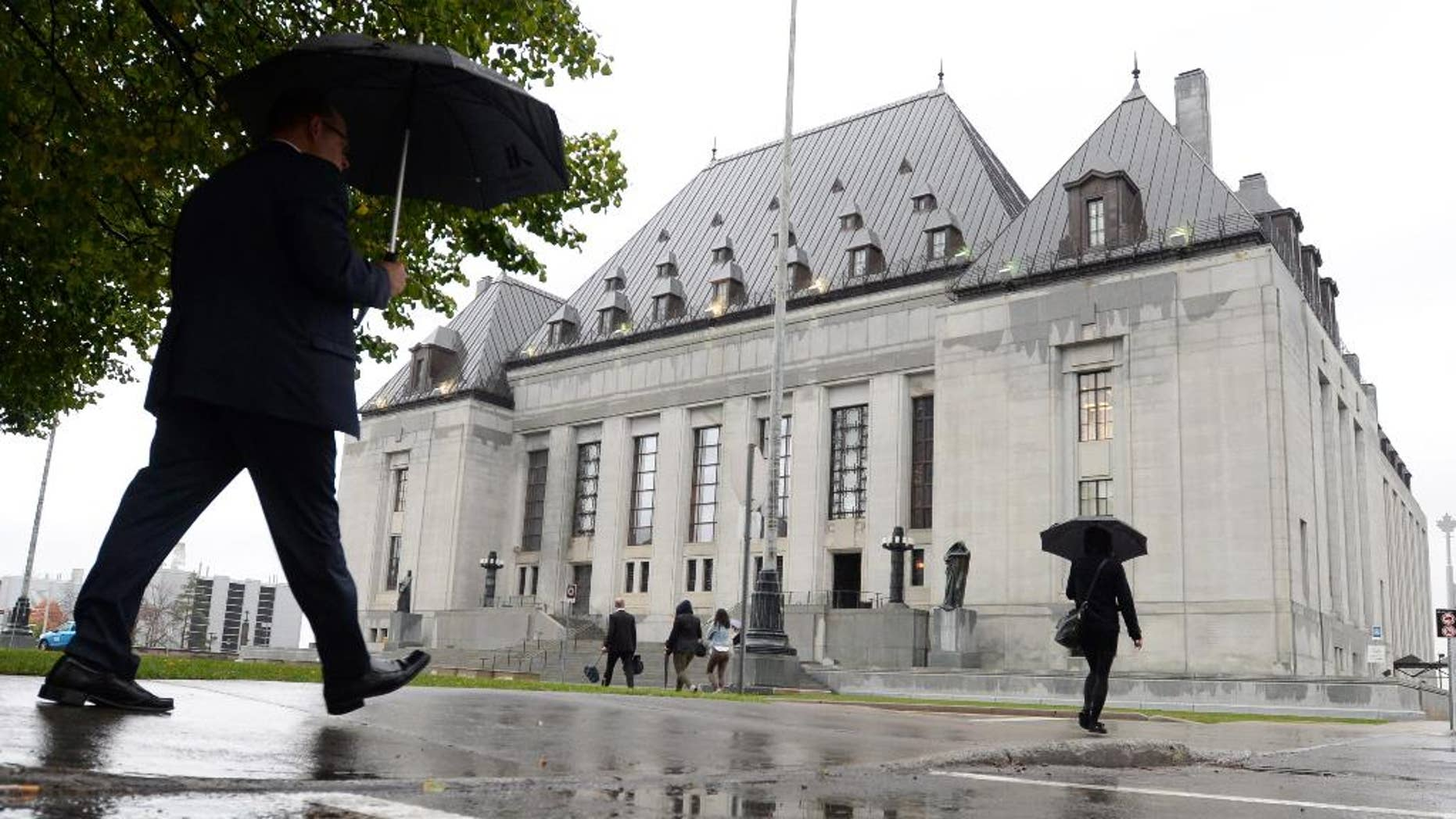 FILE - In this Oct. 15, 2014 file photo, people walk outside the Supreme Court of Canada in Ottawa, Ontario.  Canadian police can conduct a limited search of a suspect's mobile phone when they are arrested without getting a search warrant, but they must follow strict rules, a divided Supreme Court of Canada ruled Thursday, Dec. 11, 2014. In a 4-3 decision, Canada's top court said the search must be directly related to the circumstances of a person's arrest and police must keep detailed records of the search. (AP Photo/The Canadian Press, Sean Kilpatrick)