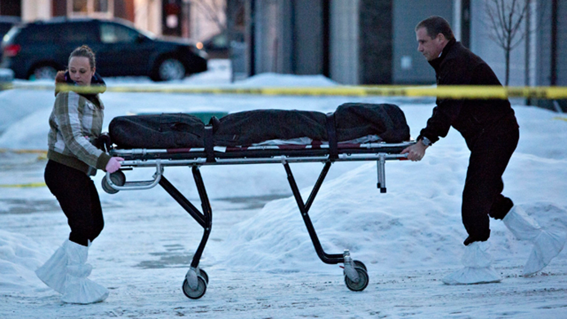 Dec. 30, 2014: The body of a victim is carried out of a north Edmonton home in Edmonton, Alberta, Canada. Nine people, including seven adults and two young children, were found dead at three separate crime scenes in what Edmonton's police chief on Tuesday called a 'senseless mass murder.' (AP Photo/The Canadian Press, Jason Franson)
