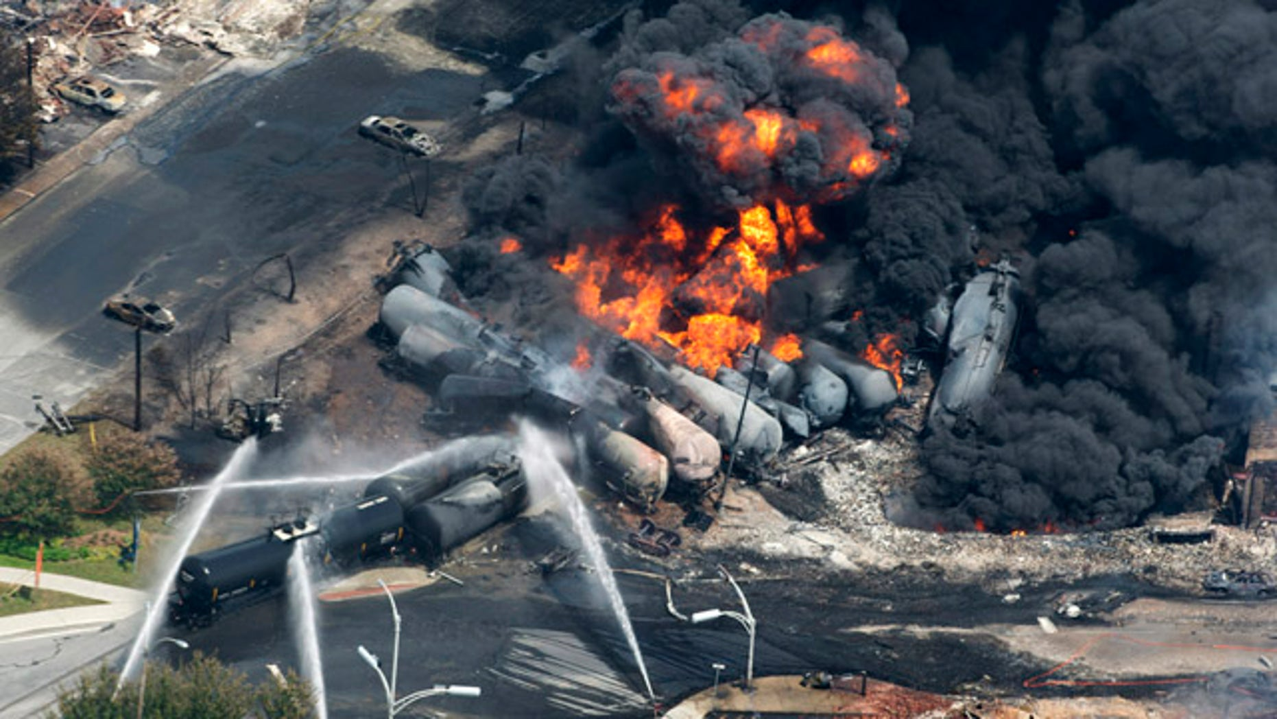 July 6, 2013: Smoke rises from railway cars that were carrying crude oil after derailing in downtown Lac Megantic, Quebec, Canada. (AP/The Canadian Press)