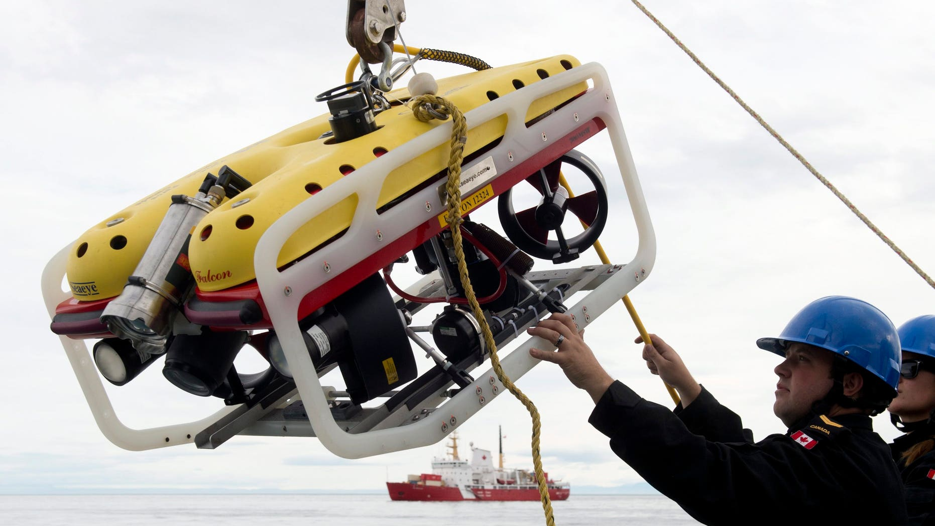 Aug. 24, 2014: A crew member of the HMCS Kingston loads an remote underwater vehicle part of the Victoria Strait Expedition, west of Pond Inlet on the Eclipse Sound.