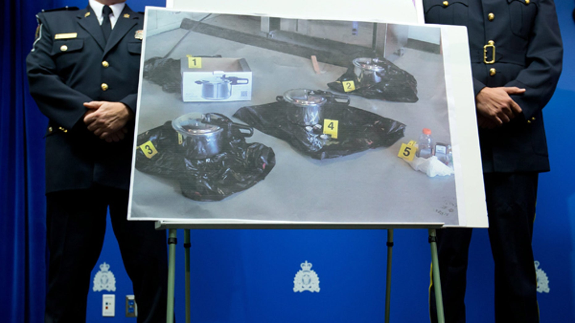 July 2, 2013: An evidence photo showing a set of pressure cookers is displayed during a news conference  in Surrey, B.C.. Police have arrested a Canadian man and a woman and charged them as terrorist suspects for attempting to leave a suspicious package at British Columbia's provincial legislature on Canada Day.