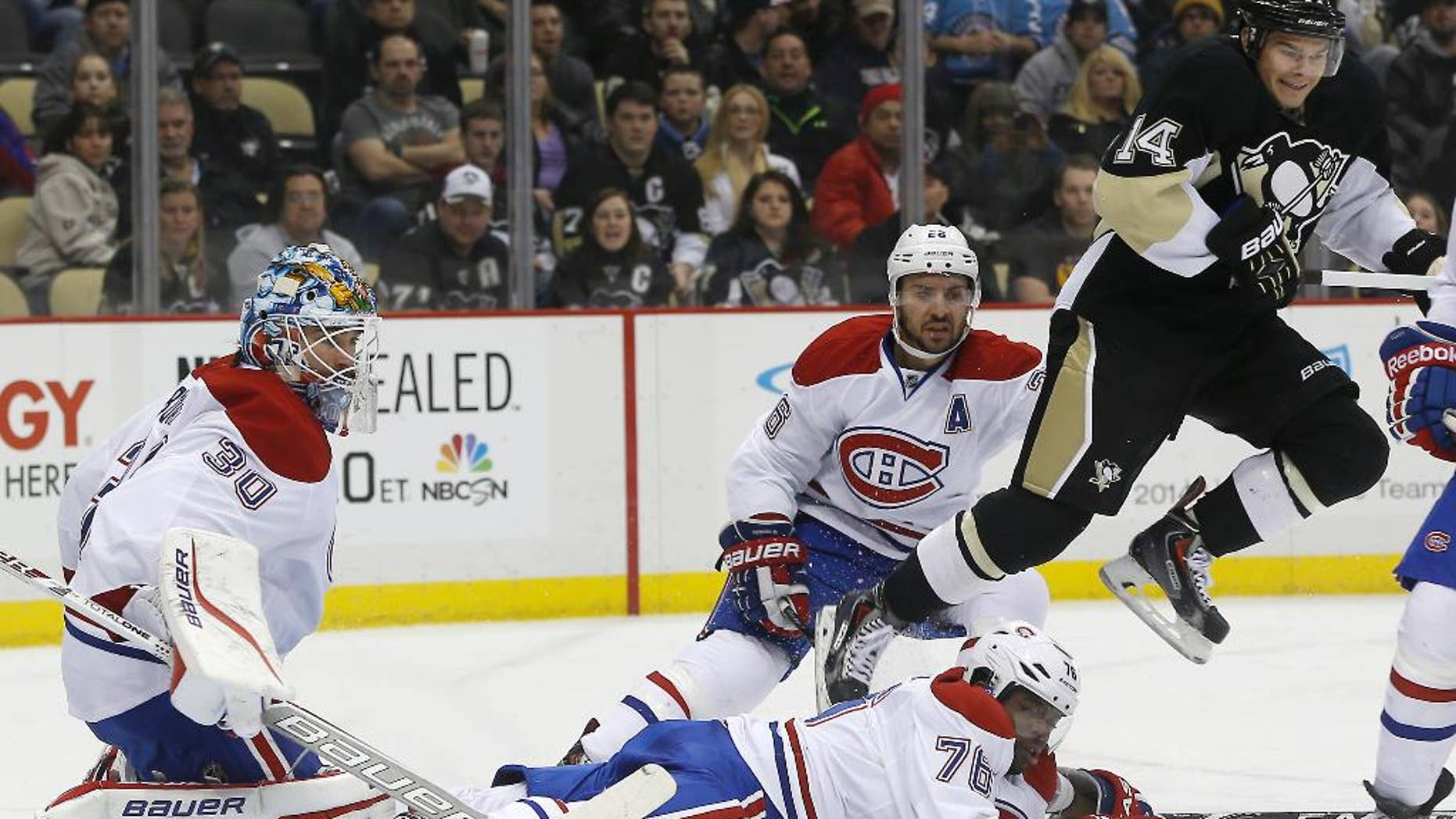 Pittsburgh Penguins' Chris Kunitz (14) hops over Montreal Canadiens' P.K. Subban (76) as he comes through the goal crease in front of goalie Peter Budaj (30), of Slovakia, during the second period of an NHL hockey game, Thursday, Feb. 27, 2014 in Pittsburgh. (AP Photo/Keith Srakocic)