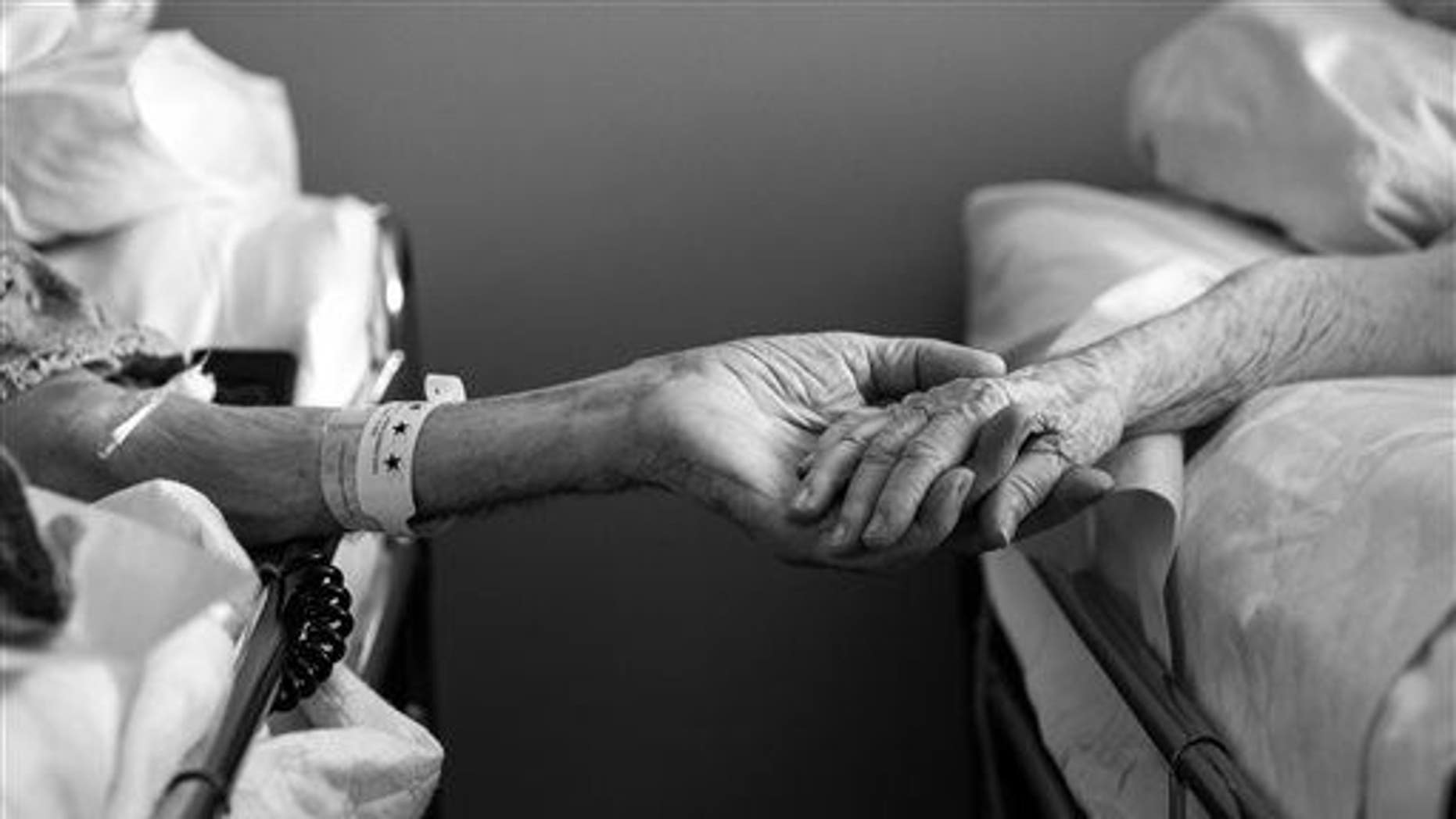 CORRECTS SOURCE TO MELISSA SLOAN INSTEAD OF MELISSA STONE - In this July, 2014 photo provided by their granddaughter, Melissa Sloan, Don Simpson, 90, and his wife Maxine, 87, hold hands from adjoining hospice beds in Sloan's home in Bakersfield, Calif. The couple, married 62 years, died four hours apart July 21, 2014, while lying next to each other, their family said. (AP Photo/Melissa Sloan)