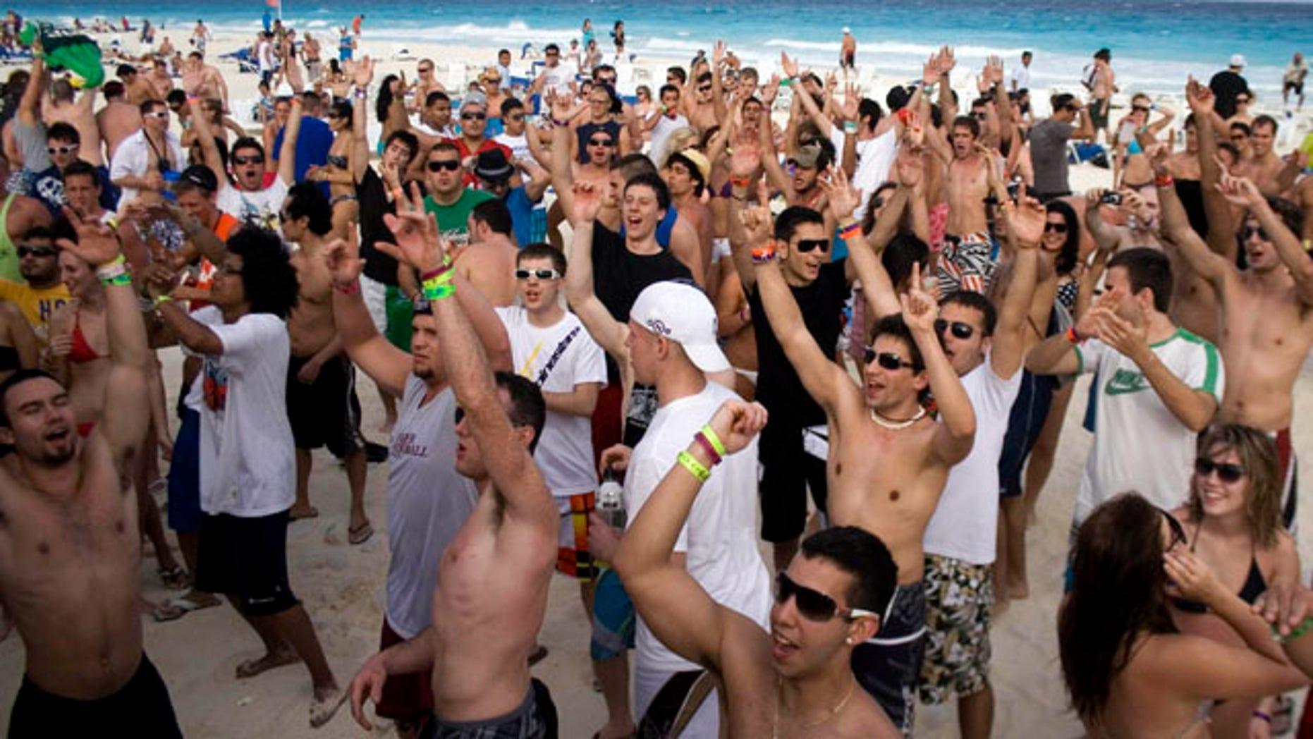 This Monday, March 1, 2010 file photo shows students on spring break cheering at the beach in the resort city of Cancun, Mexico.