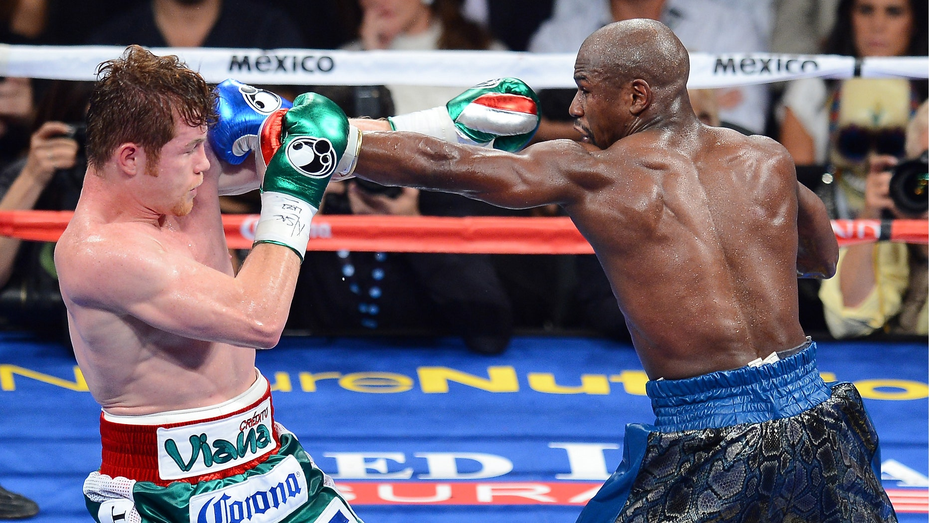 Floyd Mayweather Jr. throws a left at Canelo Alvarez at the MGM Grand Garden Arena on September 14, 2013 in Las Vegas, Nevada.