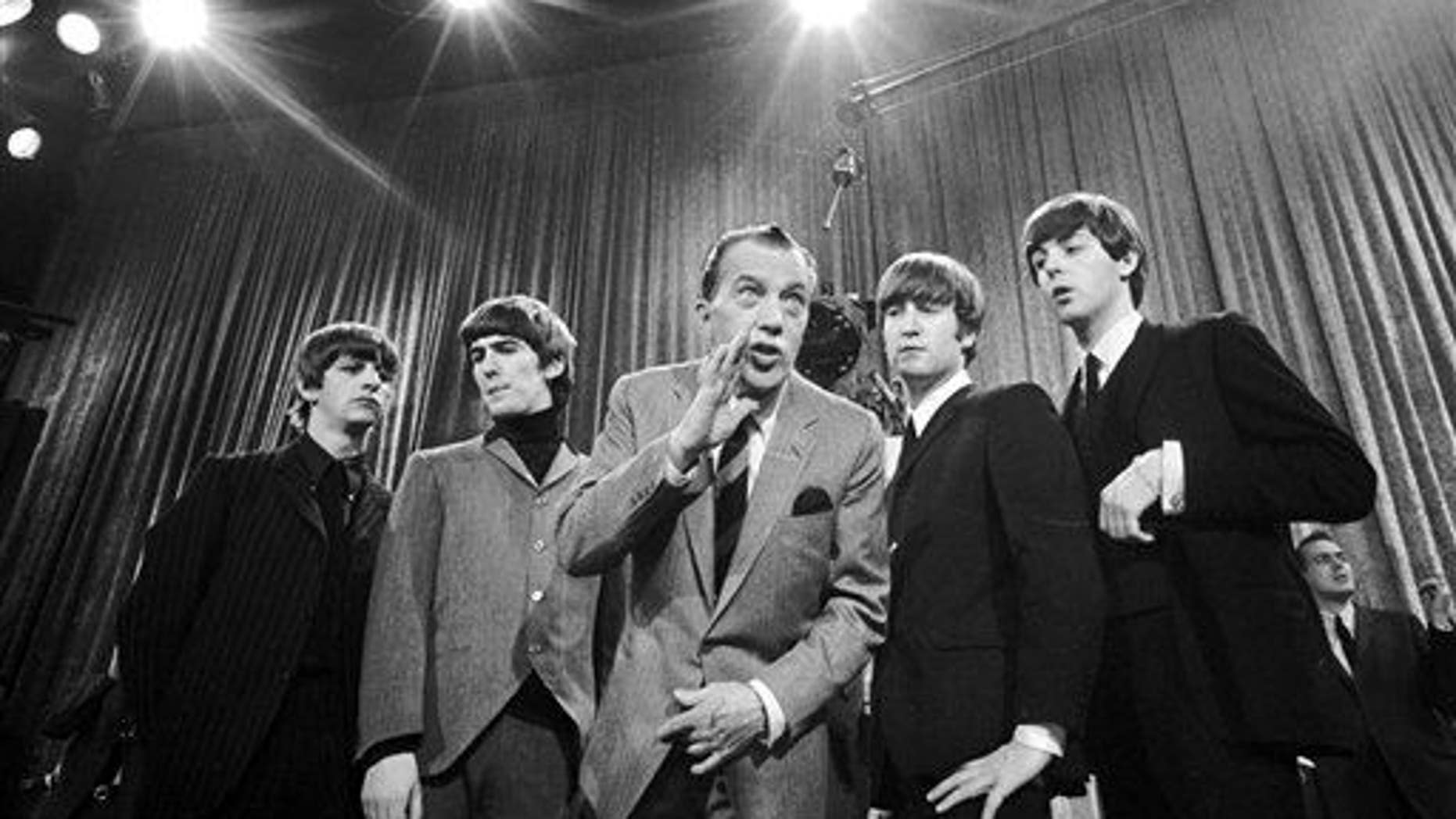 """In this Feb. 9, 1964, file photo, Ed Sullivan, center, stands with the Beatles during a rehearsal for the British group's first American appearance on """"The Ed Sullivan Show"""" in New York."""