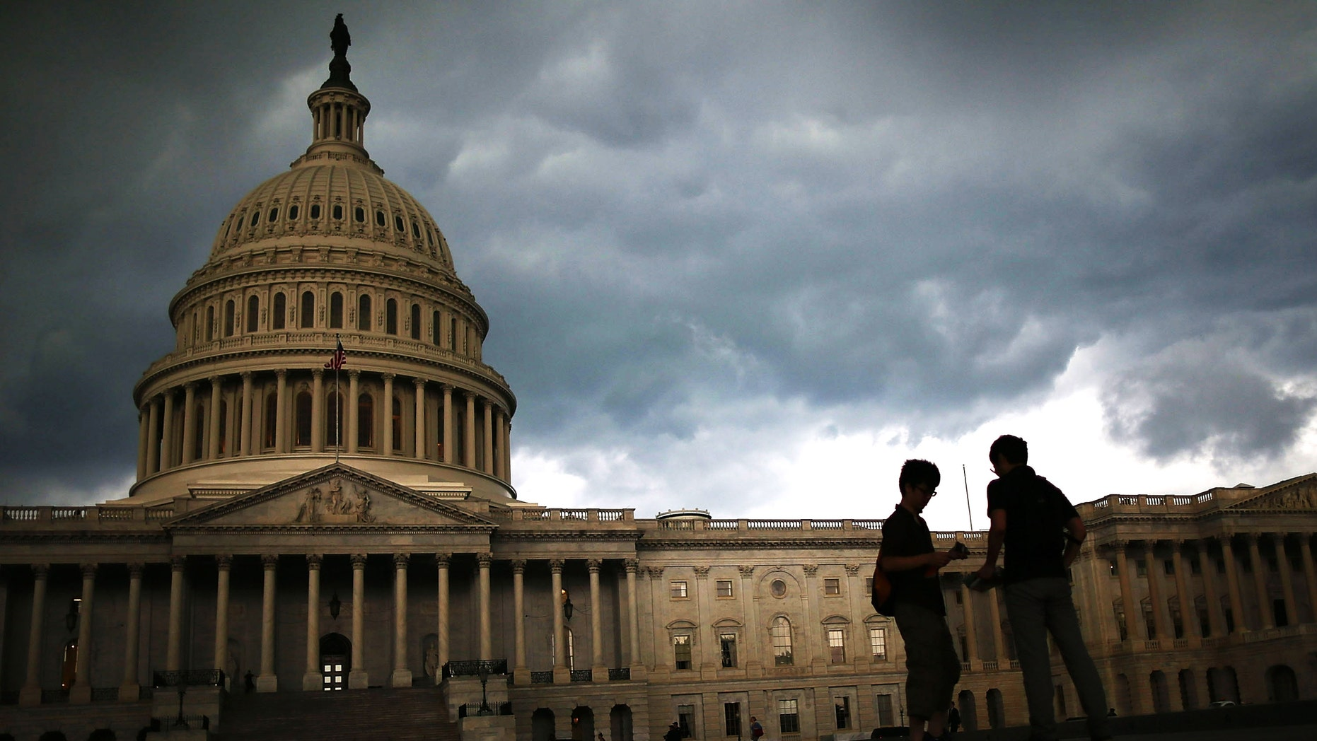 WASHINGTON, DC - JUNE 13: Two men stand on the plaza of the U.S. Capitol Building as storm clouds fill the sky, June 13, 2013 in Washington, DC. Potentially damaging storms are forecasted to hit parts of the east coast with potential for causing power wide spread outages.  (Photo by Mark Wilson/Getty Images)