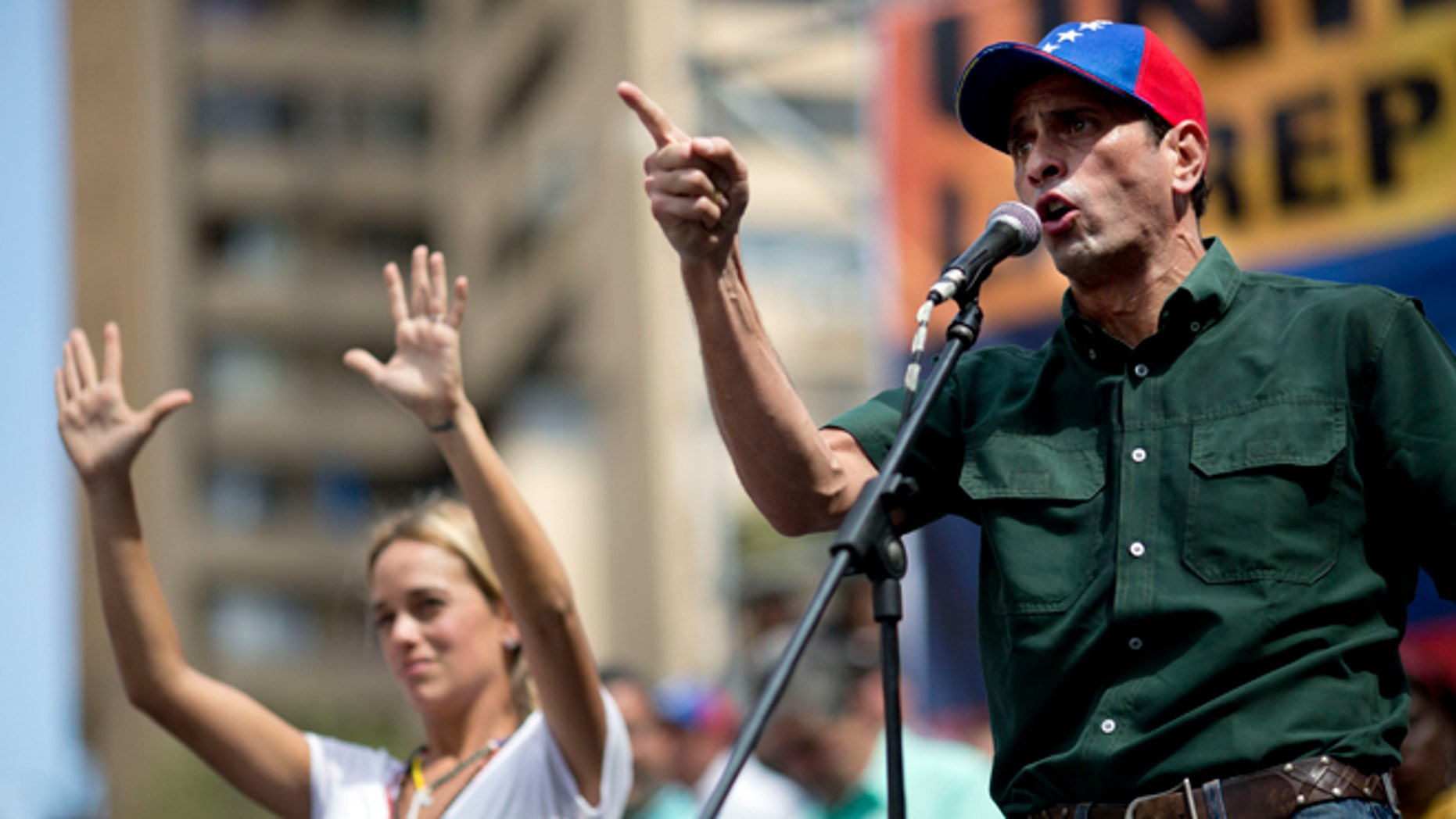 Opposition leader Enrique Capriles delivers a speech next to Lilian Tintori, wife of detained opposition leader Leopoldo Lopez, during a rally in Caracas, Venezuela, Saturday, Feb. 22, 2014. Authorities blamed opposition leader Lopez for fomenting he violence and jailed him on charges including arson and incitement, prompting anger from his supporters at home and criticism from abroad. Supporters and opponents of the government of President Nicolas Maduro are holding competing rallies in the bitterly divided country. (AP Photo/Rodrigo Abd)