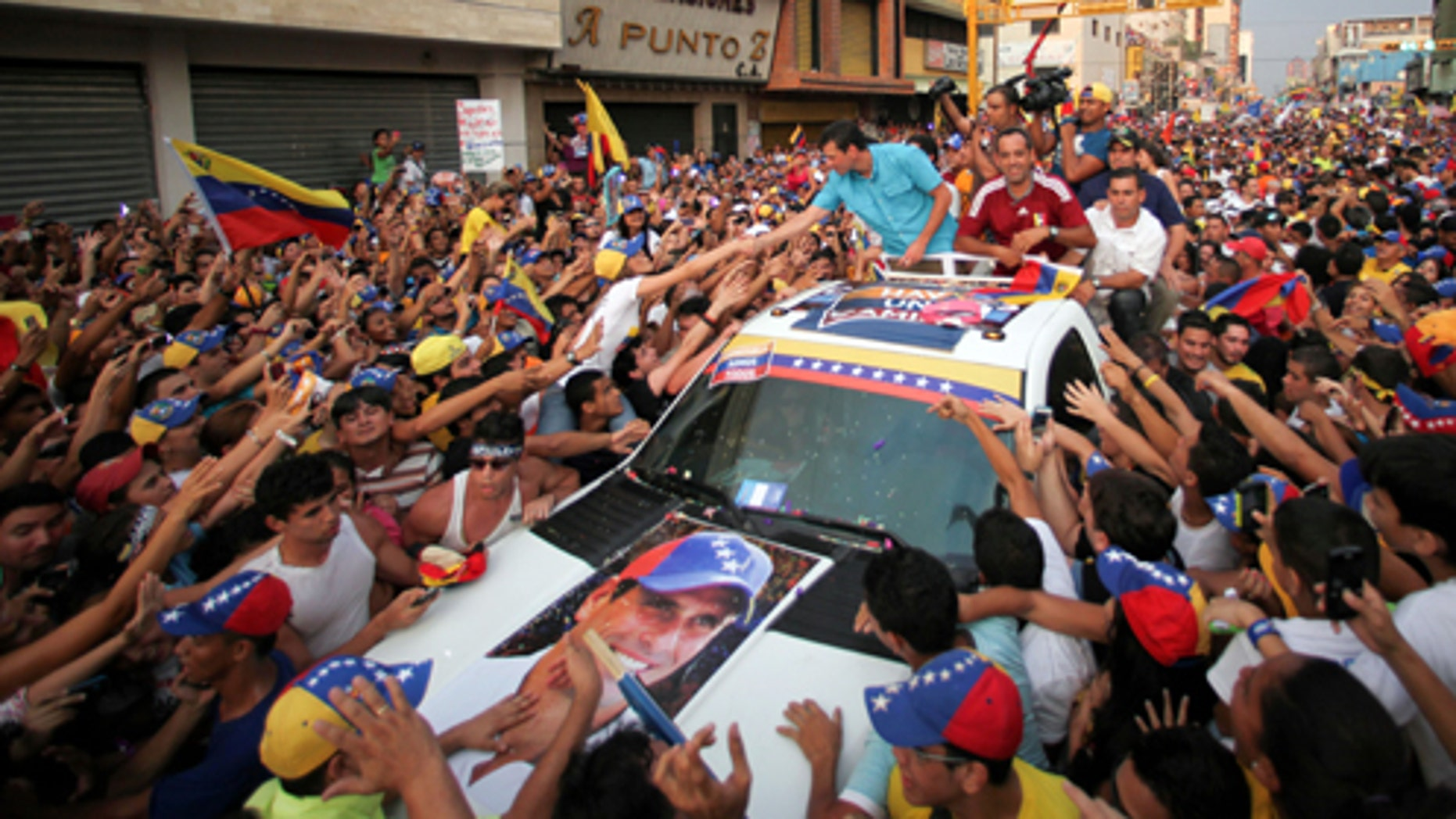 Opposition presidential candidate Henrique Capriles, center left, shakes hands with supporters while riding atop a vehicle during a campaign rally in Maracay, Venezuela, Thursday, April 4, 2013. Venezuela will hold a presidential election to replace late President Hugo Chavez on April 14. (AP Photo/Fernando Llano)