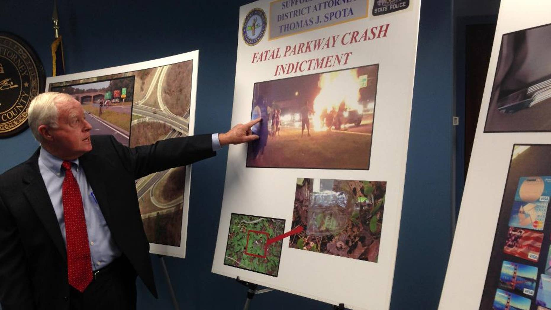 Suffolk County District Attorney Thomas J. Spota points to a photograph of the aftermath of a July 12, 2015, car crash on the Southern State Parkway that killed a father and his two children, Thursday, Aug. 27, 2015 in Hauppauge, N.Y. The prosecutor announced criminal charges Thursday against four people allegedly involved in the crash. All four have pleaded not guilty. (AP Photo/Frank Eltman)