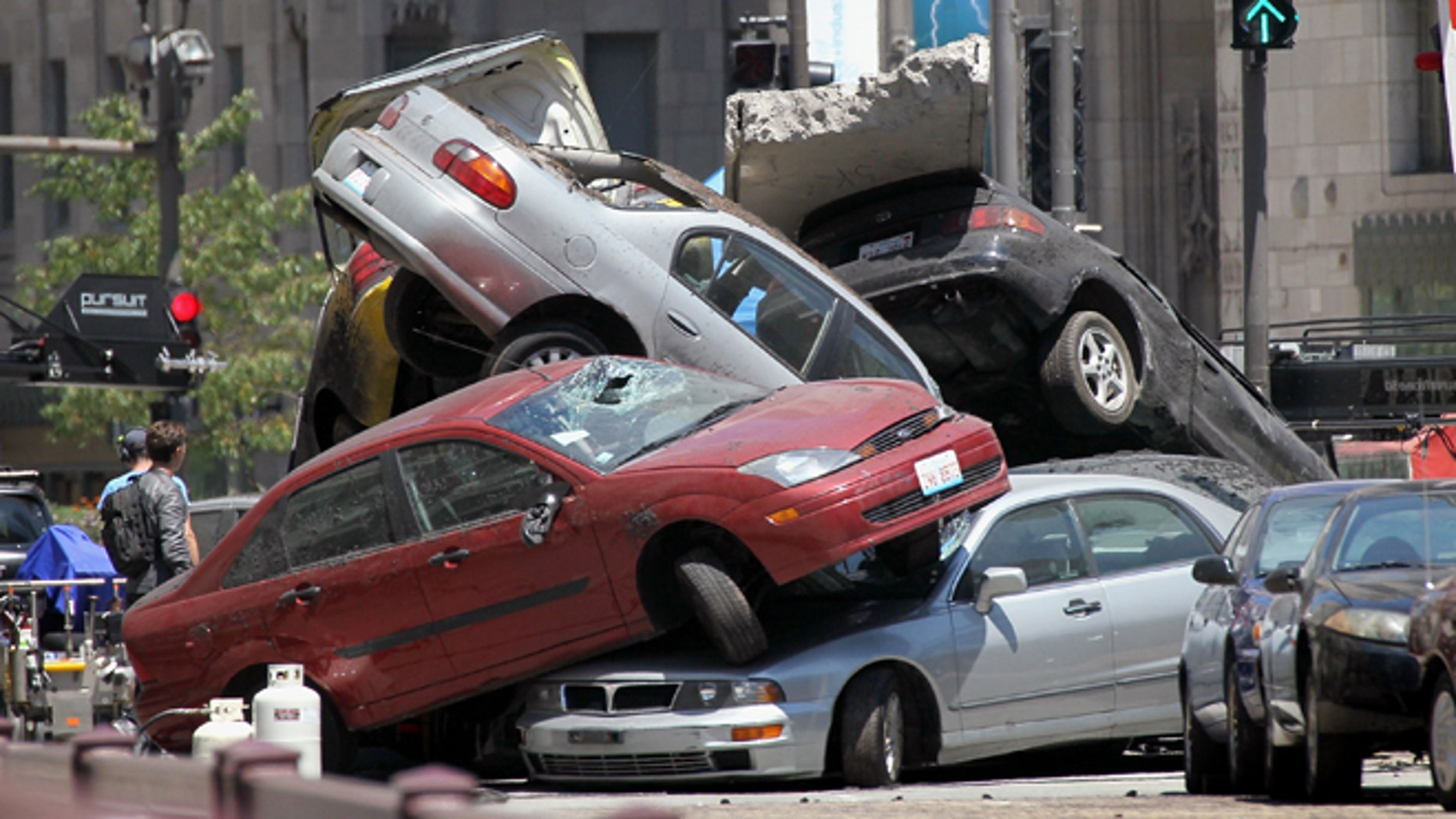 """Workers stage a car accident during the filming of the movie """"Transformers 3"""" in Chicago, Illinois."""