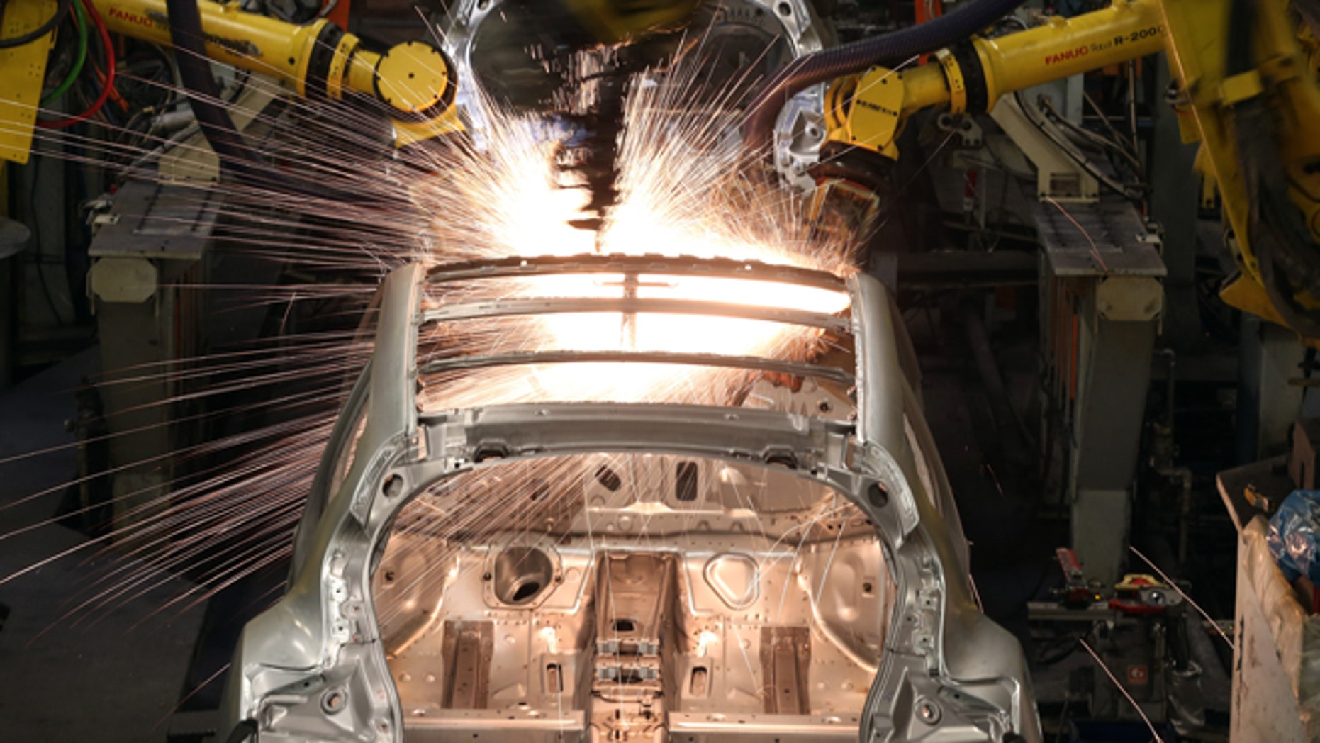 Robotic arms assemble and weld the body shell of a Nissan car on the production line. (Photo by Christopher Furlong/Getty Images)