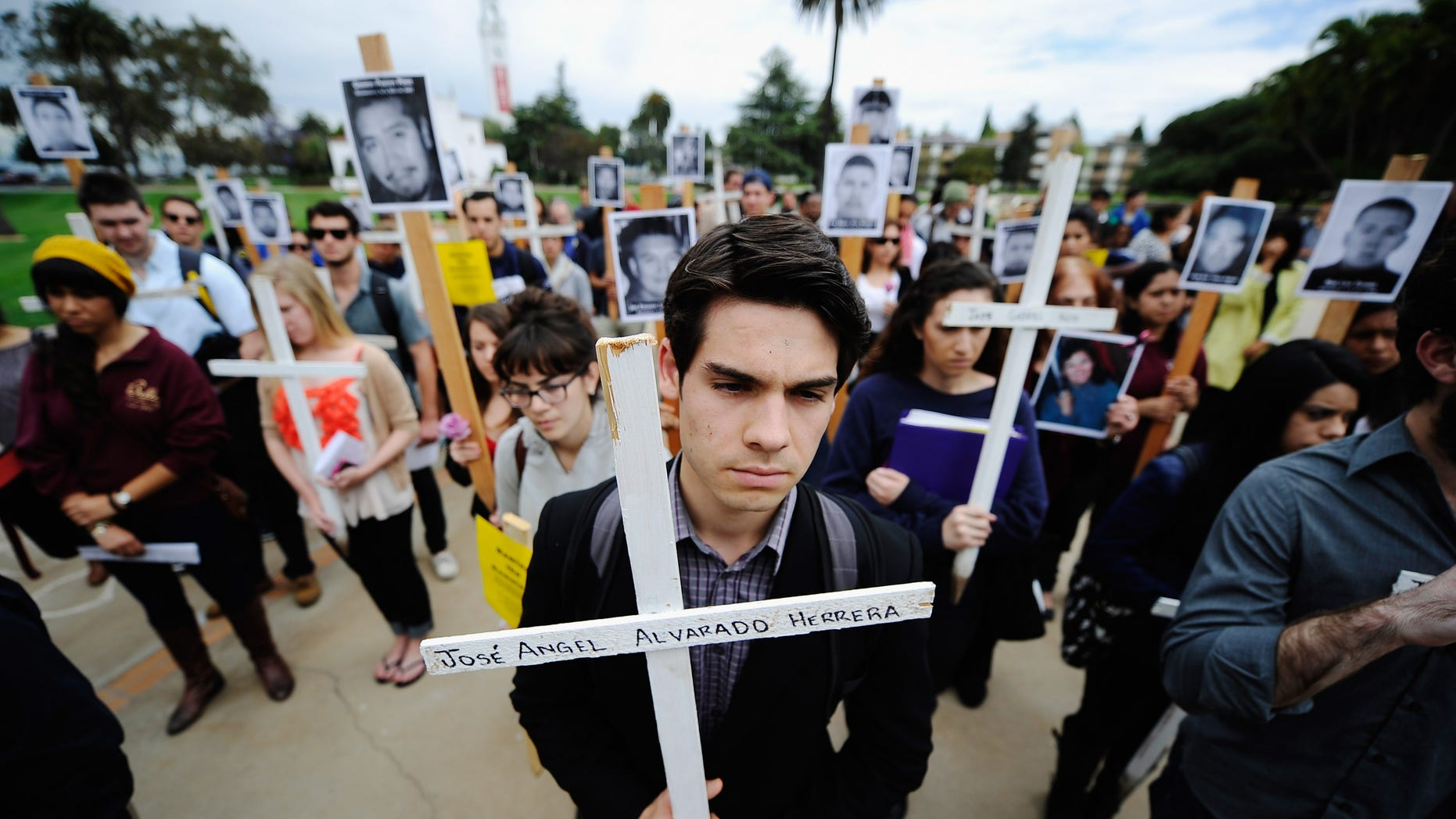 Loyola Marymount University student Michael Mardinkian takes part in a 50-cross procession on the university campus on April 25, 2012 in Los Angeles, California. The procession was led by Javier Sicilia, poet and leader of the Mexican anti-drug group Movement for Peace with Justice and Dignity, to raise awareness on the drug wars in Mexico and the United States to protest drug-related killings, with each cross representing 1,000 victims. (Photo by Kevork Djansezian/Getty Images)