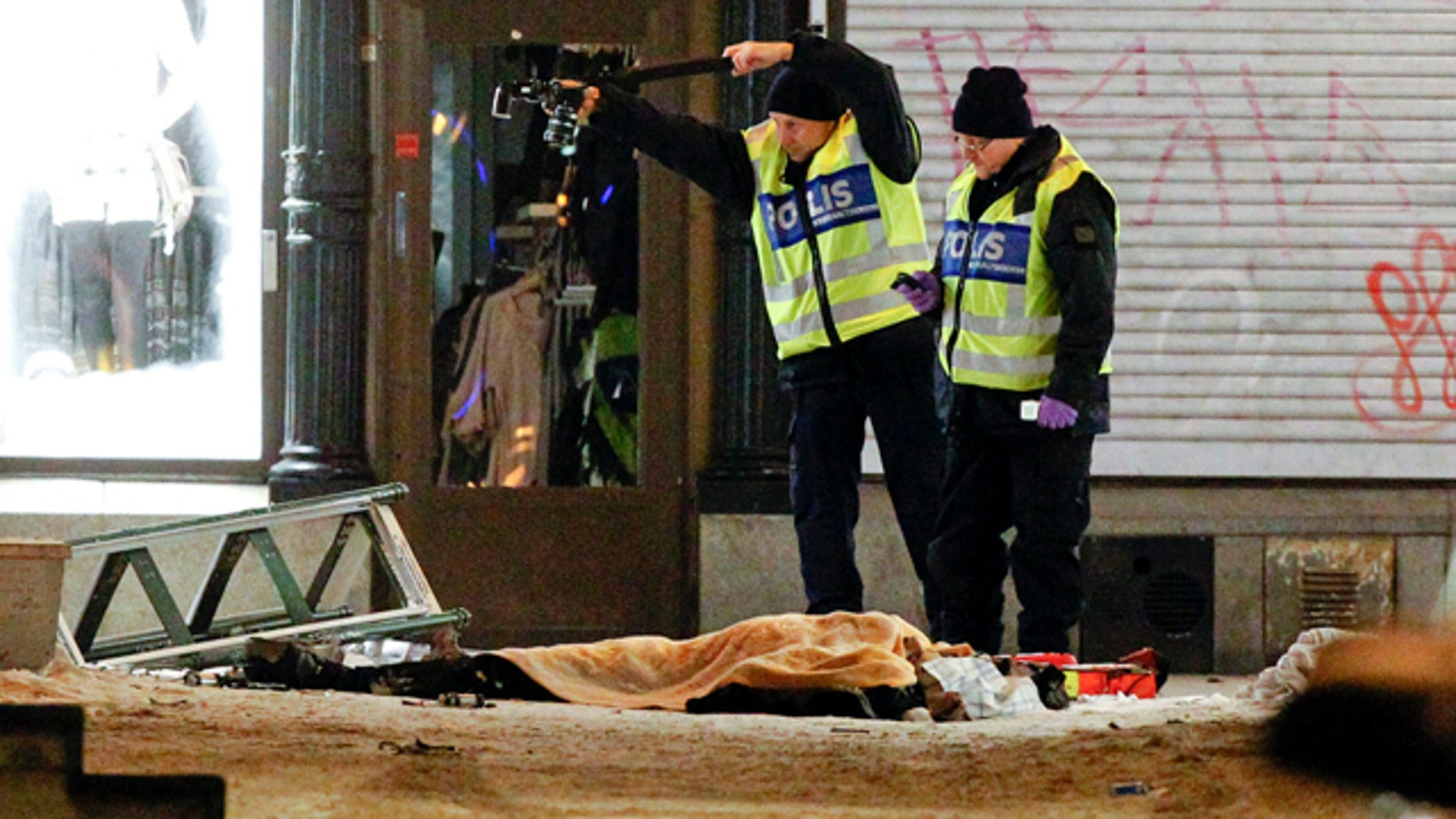 Police forensics experts examine the scene in Stockholm after an apparent suicide attack
