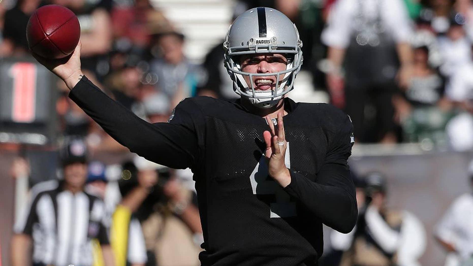 Oakland Raiders quarterback Derek Carr (4) passes against the Arizona Cardinals during the second half of an NFL football game in Oakland, Calif., Sunday, Oct. 19, 2014. The Cardinals won 24-13. (AP Photo/Marcio Jose Sanchez)