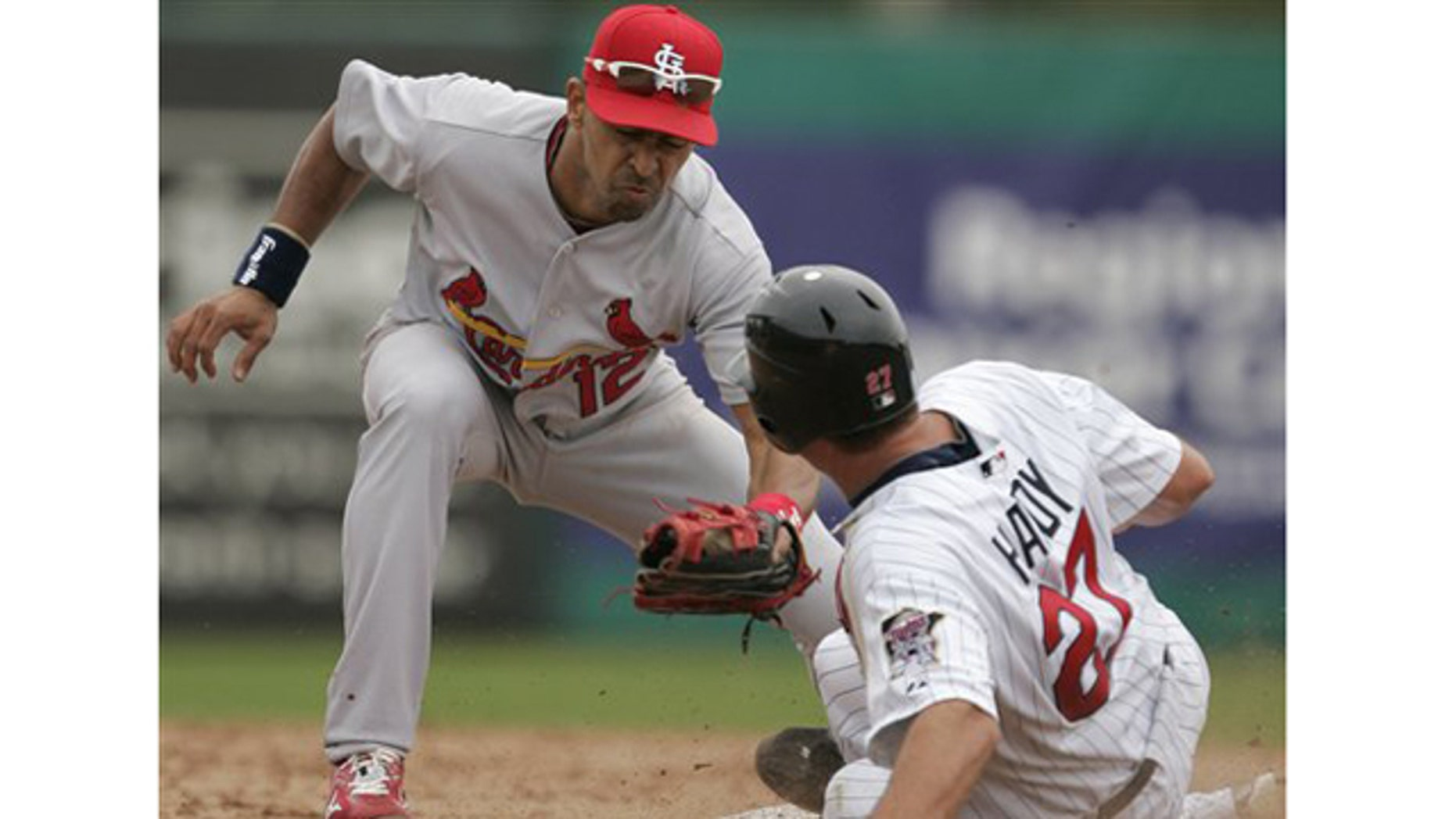 St. Louis Cardinals shortstop Julio Lugo tries to tag Minnesota Twins' J.J. Hardy who steals second base in the second inning of a spring training baseball game in Fort Myers, Fla., Tuesday, March 9, 2010.