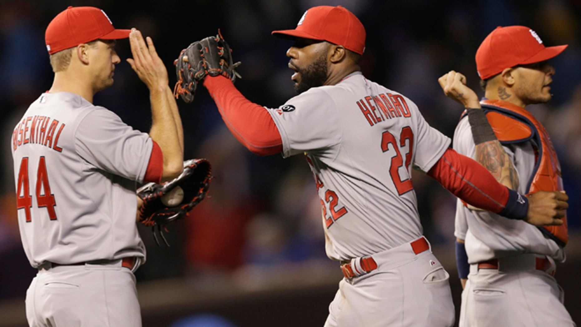 St. Louis Cardinals right fielder Jason Hayward, center, celebrates with closer Trevor Rosenthal, left, and catcher Yadier Molina after the St. Louis Cardinals defeated the Chicago Cubs 3-0 in a Major League Baseball season-opening game in Chicago, Sunday, April 5, 2015. (AP Photo/Nam Y. Huh)