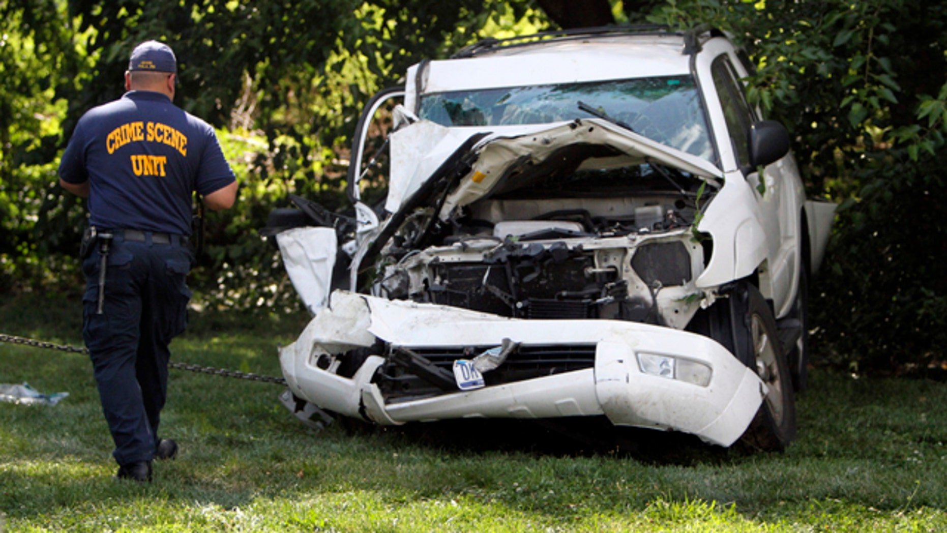 July 25, 2014: An investigator examines a heavily damaged SUV before it is towed from the scene of a fatal accident in North Philadelphia. Two children were killed and three people critically injured when a hijacked car lost control and hit a group of people near a fruit stand, according to police. (AP Photo/ Joseph Kaczmarek)