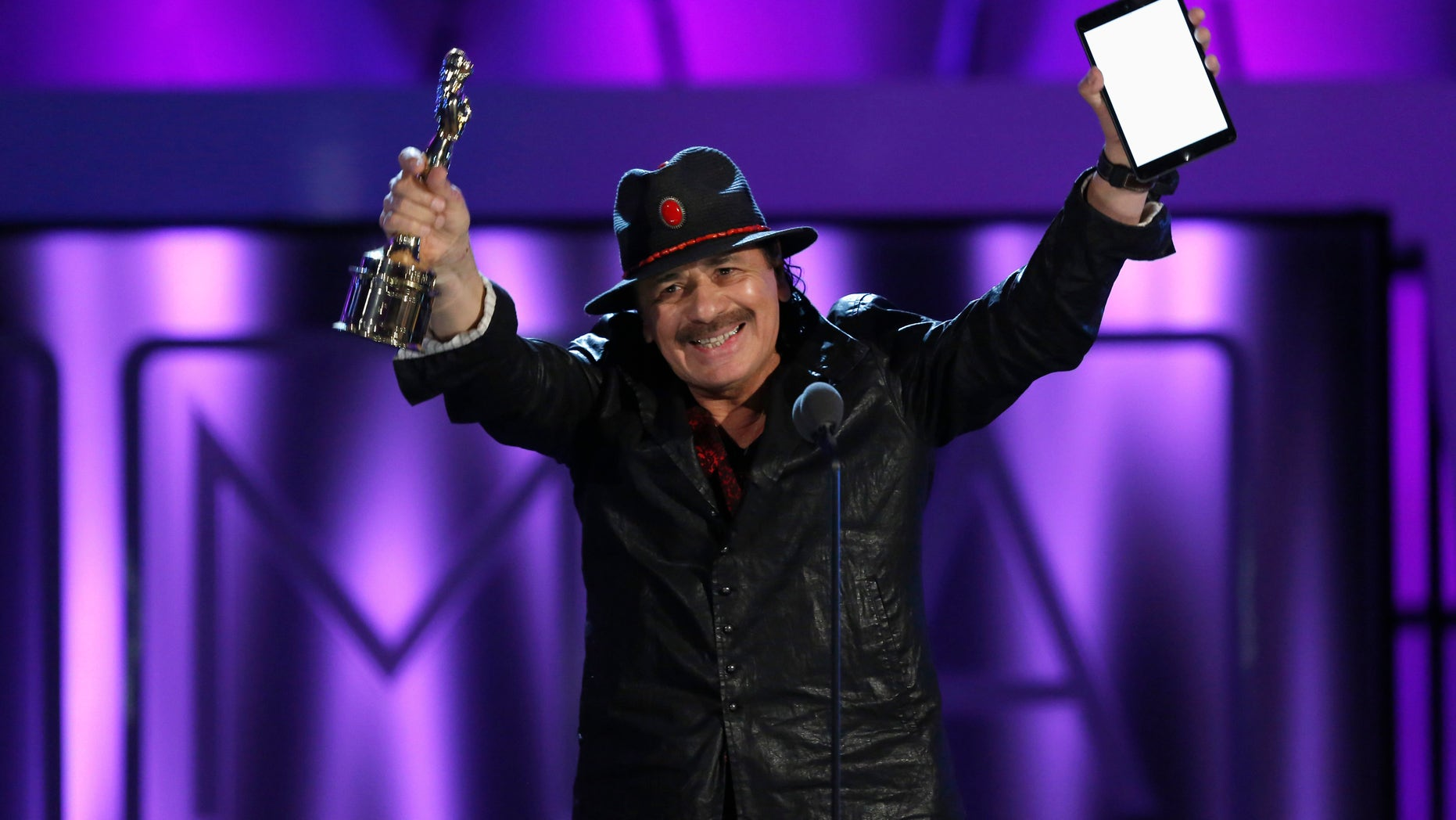 Musician Carlos Santana accepts the Outstanding Commitment to Cause and Community Award at the 2013 NCLR ALMA Awards at the Pasadena Civic Auditorium in Pasadena, California September 27, 2013.