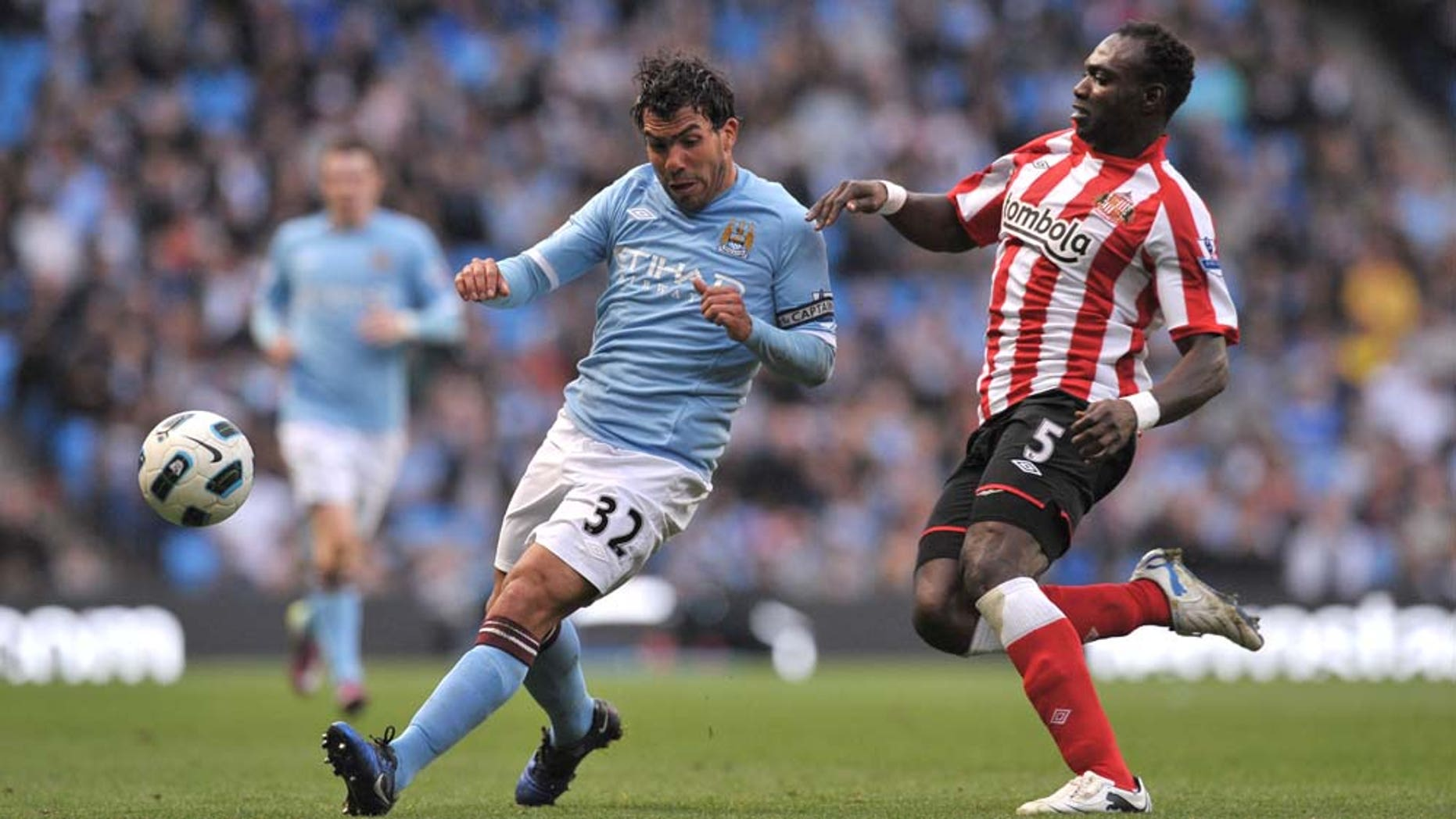 Manchester City's Carlos Tevez, left, keeps the ball from Sunderland's John Mensah during their English Premier League soccer match at The City of Manchester Stadium, Manchester, England, Sunday April 3, 2011. (AP Photo/Jon Super)   NO INTERNET/MOBILE USAGE WITHOUT FOOTBALL ASSOCIATION PREMIER LEAGUE(FAPL)LICENCE. EMAIL info@football-dataco.com FOR DETAILS.