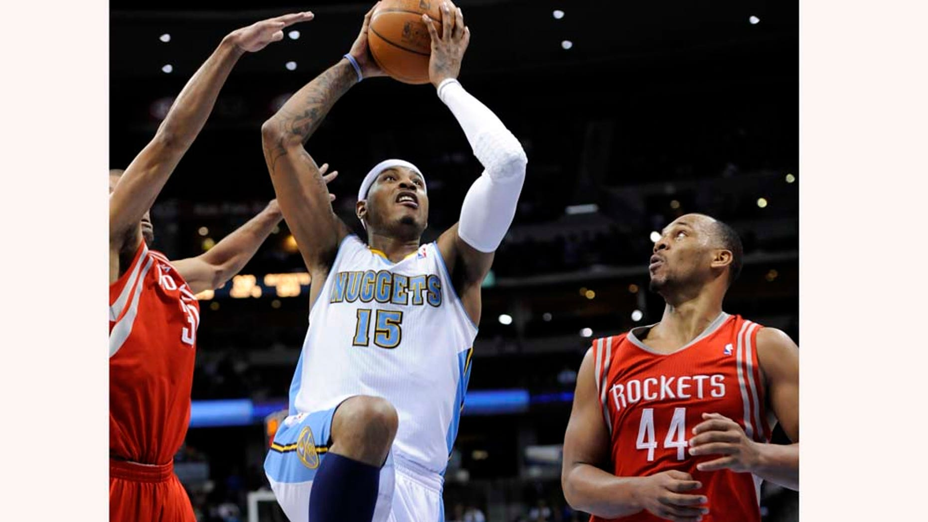 Denver Nuggets forward Carmelo Anthony (15) goes up for a shot against Houston Rockets center Chuck Hayes (44) during the fourth quarter of an NBA basketball game on  Monday, Feb. 7, 2011, in Denver. Houston beat Denver 108-103. (AP Photo/Jack Dempsey)