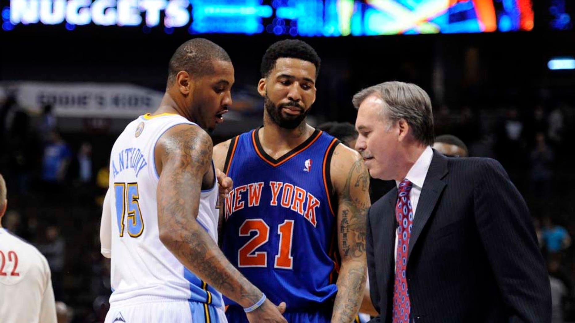 FILE - This Nov. 16, 2010, file photo shows New York Knicks head coach Mike D'Antoni shaking hands with Denver Nuggets forward Carmelo Anthony (15) as New York Knicks forward Wilson Chandler (21) looks on following an NBA basketball game, in Denver. Listening to Nets coach Avery Johnson, the monster deal to bring Anthony from Denver to New Jersey might be on hold. Hours before leaving for a four-game West Coast road trip, Johnson said Tuesday, Jan. 11, 2011,  he didn't expect any roster changes during the trip. (AP Photo/Jack Dempsey, File)