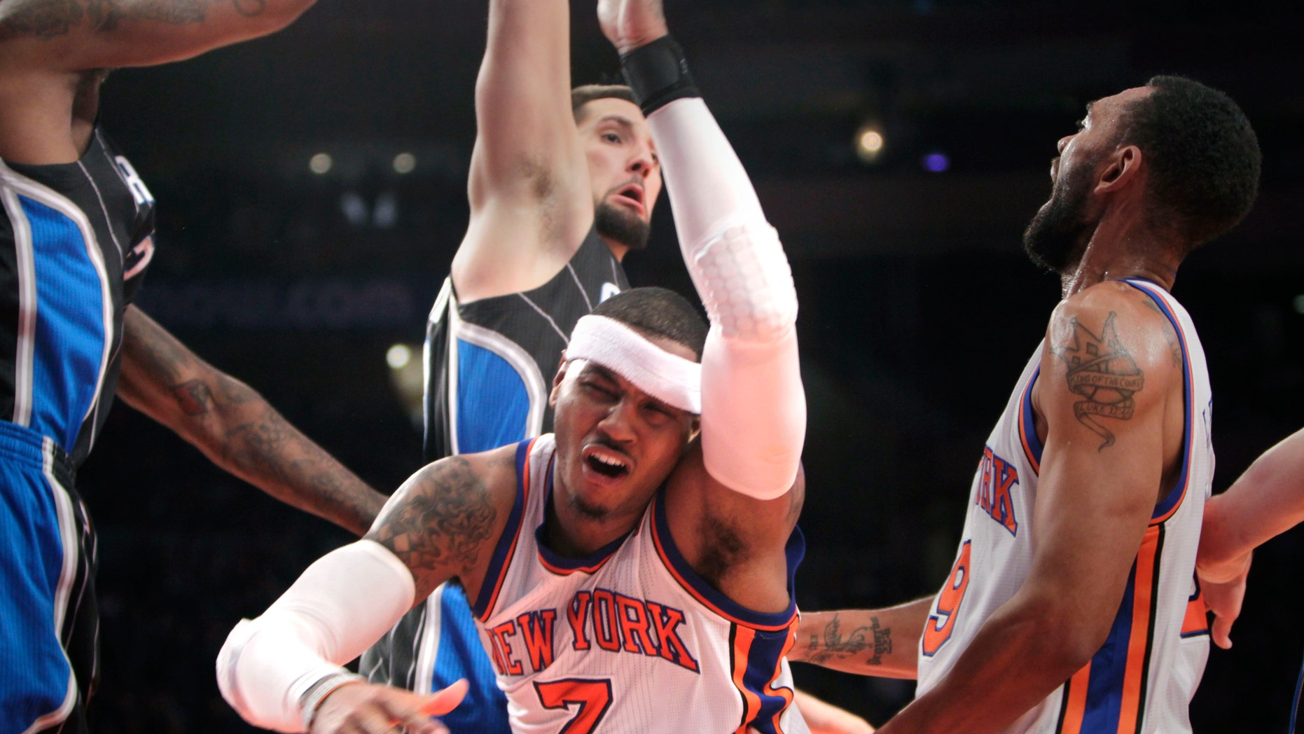 New York Knicks' Carmelo Anthony, center, is knocked down while going for a basket during the first half of an NBA basketball game in New York, Monday, Jan. 16, 2012.  (AP Photo/Seth Wenig)