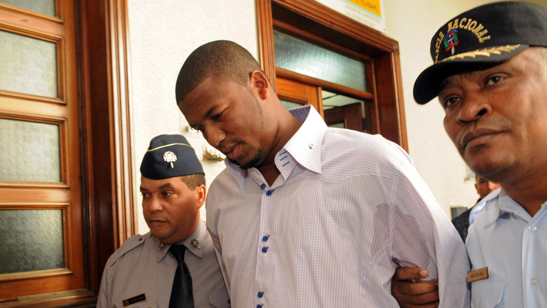 Cleveland Indians pitcher Fausto Carmona, whose real name is Roberto Hernandez Heredia, center, is escorted by police out of court in Santo Domingo, Dominican Republic, Friday Jan. 20, 2012. Hernandez made a tearful apology as he was released on bail following his arrest on Thursday outside the U.S. Consulate in the Dominican capital as he went to get his visa renewed, for allegedly using a false identity to play baseball in the U.S. He is the second Dominican player arrested in recent weeks for using a false identity. (AP Photo/Manuel Diaz)