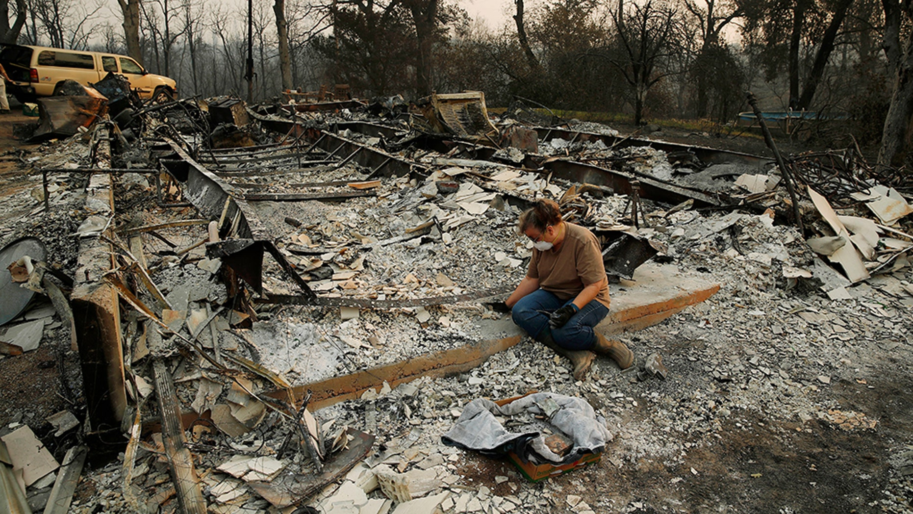 Kim Burns sifting through the charred rubble of her home burned in the Carr Fire, Sunday, Aug. 12, 2018, in Redding, Calif.