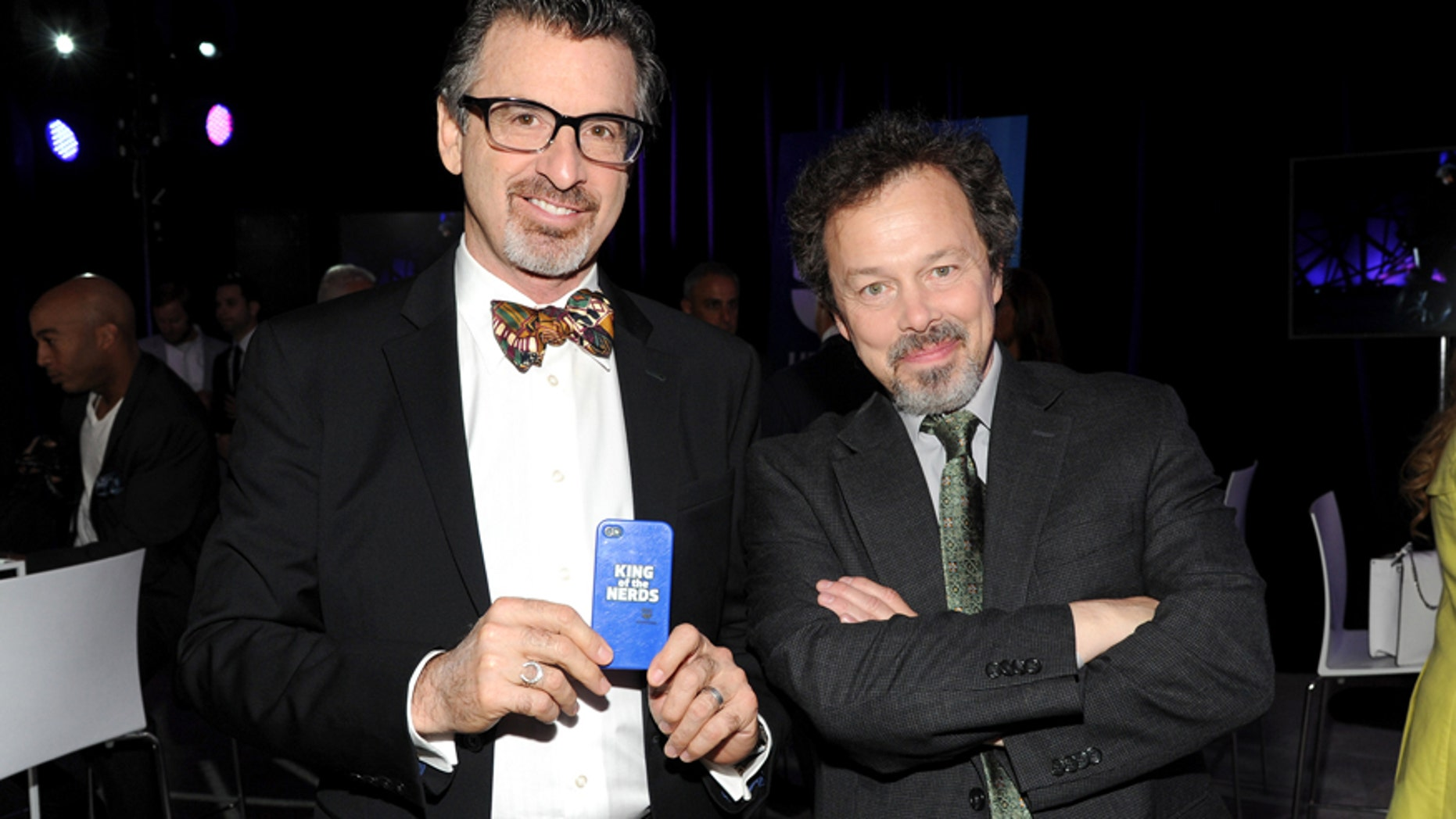 """FILE - In this May 15, 2013 file photo, """"King of the Nerds"""" co-hosts Robert Carradine, left, and Curtis Armstrong attend the TNT and TBS 2013 Upfront at the Hammerstein Ballroom, in New York."""