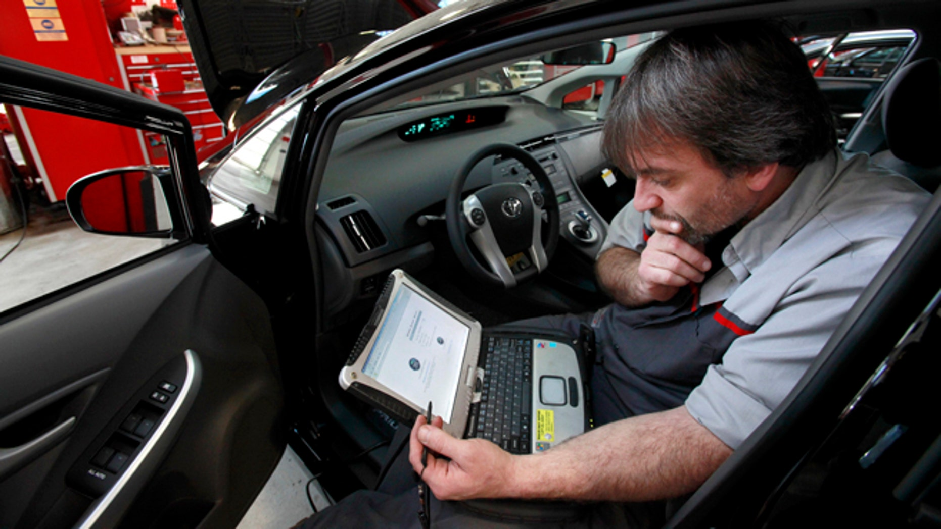 FILE - In this Feb. 9, 2010 file photo, master diagnostic technician Kurt Juergens, of Foxborough, Mass., uses a laptop computer to diagnose and repair the brake system on a 2010 Toyota Prius in the repair shop of a Toyota dealership, in Norwood, Mass. A pair of hackers maneuvered their way into the computer systems of a 2010 Toyota Prius and 2010 Ford Escape through a port used by mechanics. The hackers showed that they could slam on the brakes at freeway speeds, jerk the steering wheel or even shut down the engine, all from their laptop computers. The work demonstrates vulnerabilities with the growing number of car computers, about 20 on older models and up to 70 on sophisticated luxury cars. (AP Photo/Steven Senne, File)