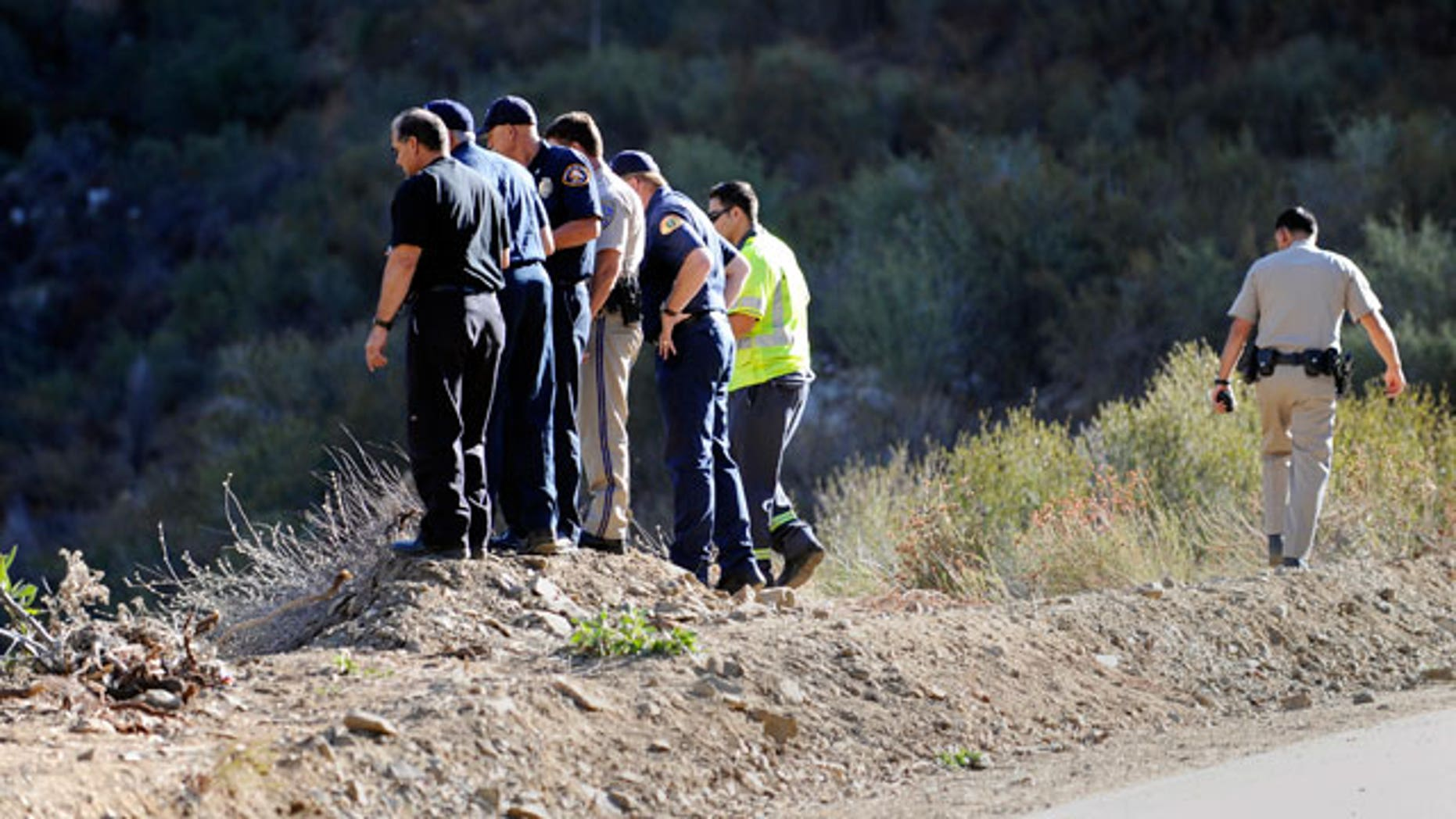 California Highway patrol officers investigate the scene of two cars that were recovered at the bottom of a remote mountain in Castaic, Calif., Friday, Sept. 30, 2011 .
