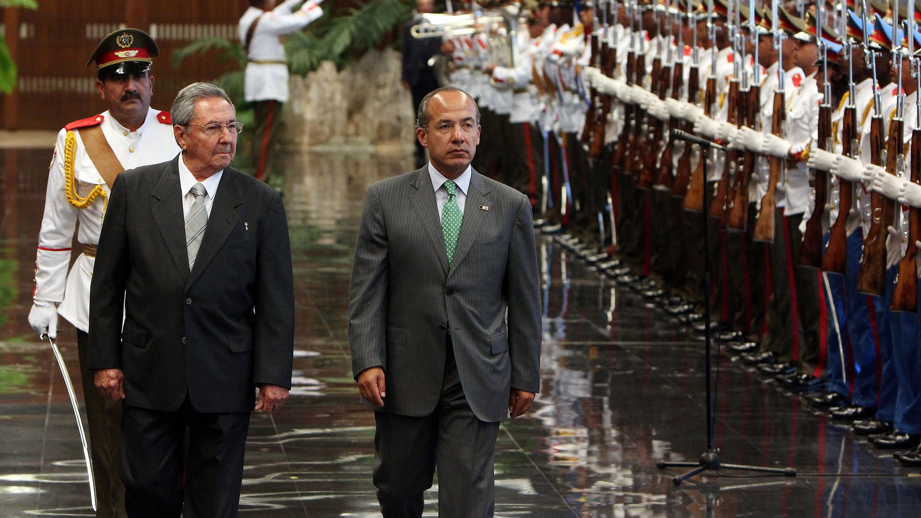 Cuba's President Raul Castro, front left, and Mexico's President Felipe Calderon review a honor guard during a ceremony at the Revolution palace in Havana, Cuba, Wednesday, April 11, 2012. Calderon is on a two-day official visit to Cuba. (AP Photo/Alejandro Ernesto, Pool)