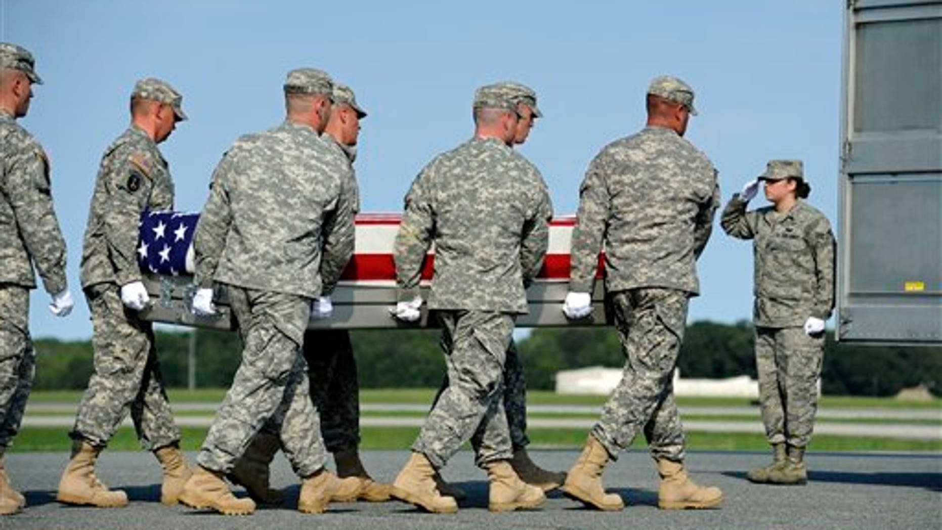 August 29: An Army carry team carries the transfer case containing the remains of Army Pfc. Jesse W. Dietrich, 20, of Venus, Texas, at Dover Air Force Base, DE.