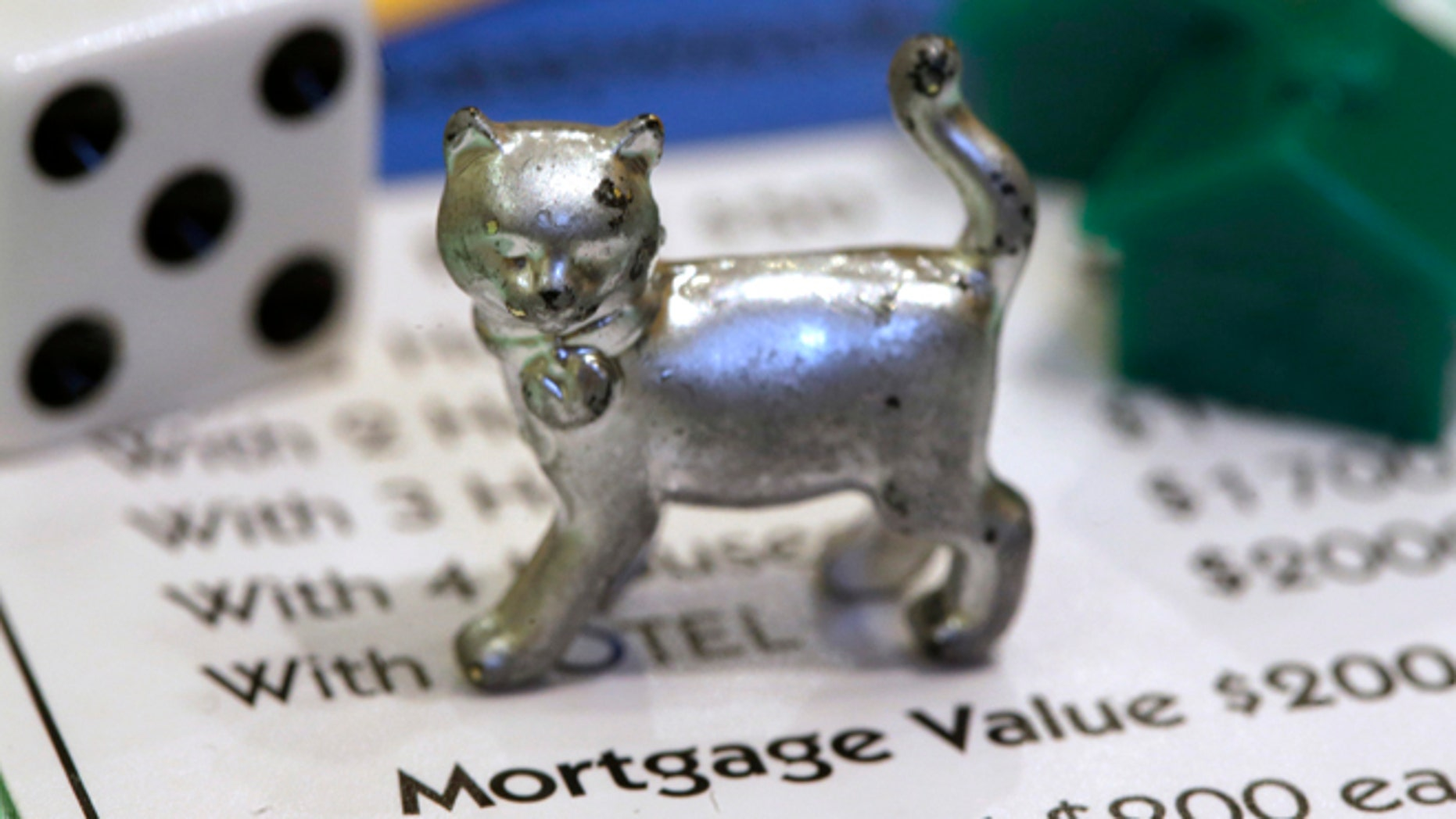 Feb. 5: The newest Monopoly token, a cat, rests on a Boardwalk deed next to a die and houses at Hasbro Inc. headquarters, in Pawtucket, R.I.