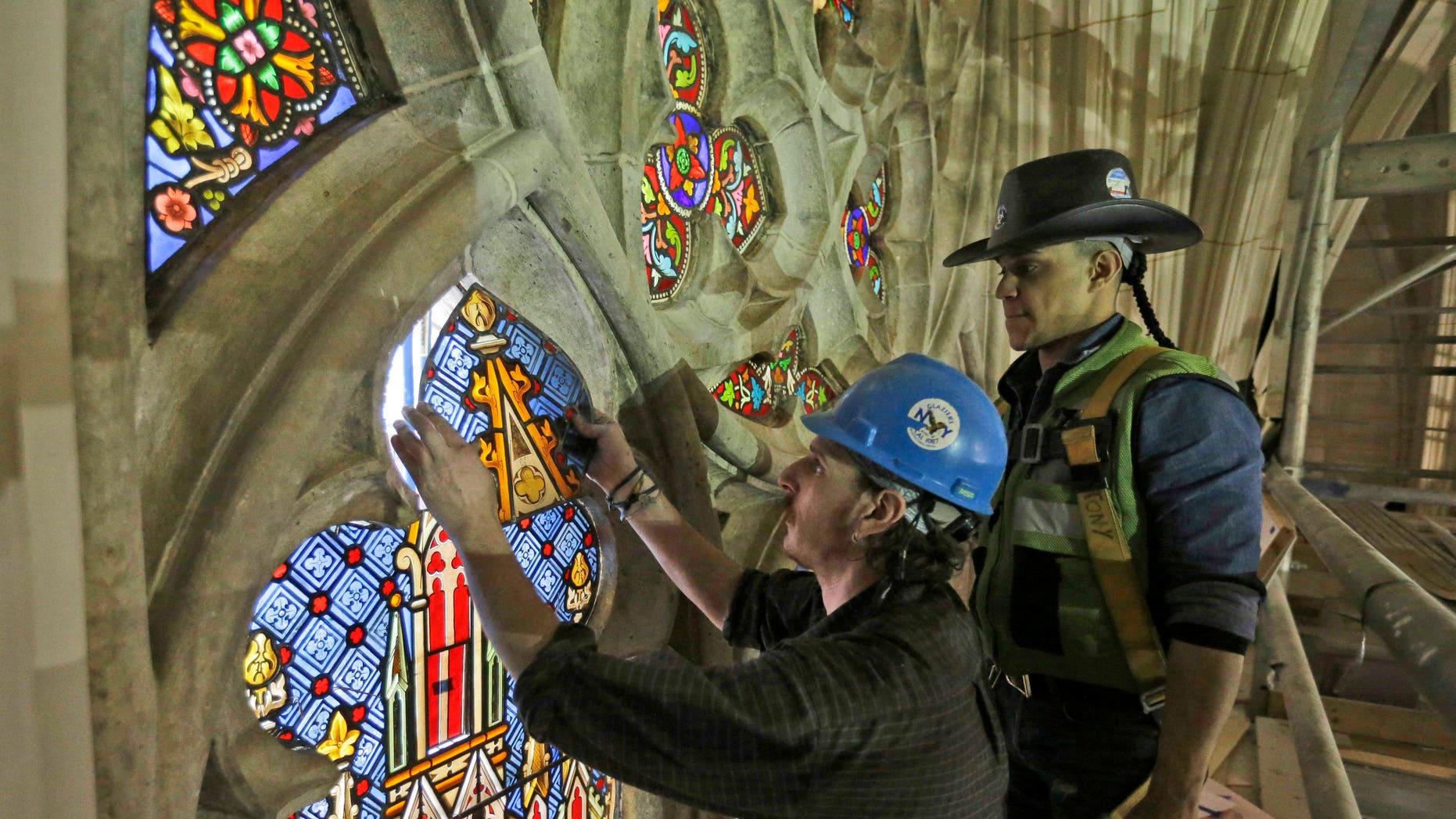 In this Wednesday, May 6, 2015 photo, master craftsman Todd Allen, left, and foreman Anthony Del Orbe install a restored stained glass panel at St. Patrick's Cathedral in New York. Workers cleaned and repaired the 3,700 individual panels in 75 stained glass windows, among other extensive renovation work. A three-year restoration project at the cathedral is coming to an end, just in time for a late September visit from Pope Francis. (AP Photo/Mary Altaffer)