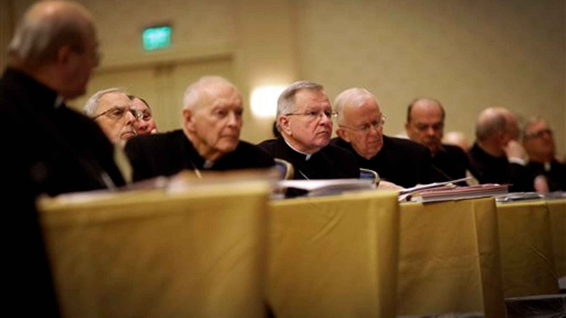 Archbishop Gregory Aymond of New Orleans, center, listens to a report as he sits with fellow bishops at the United States Conference of Catholic Bishops' annual fall meeting in Baltimore, Monday, Nov. 11, 2013, their first national meeting since Pope Francis was elected. (AP Photo/Patrick Semansky)