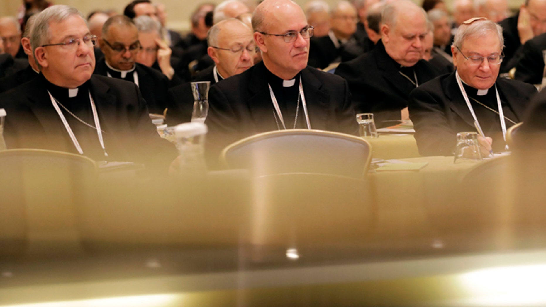 Members of the United States Conference of Catholic Bishops are seen above reflections on a piano as they attend the USCCB's annual fall meeting in Baltimore, Monday, Nov. 14, 2016. The bishops opened their meeting by urging President-elect Donald Trump to adopt humane policies toward immigrants and refugees. (AP Photo/Patrick Semansky)