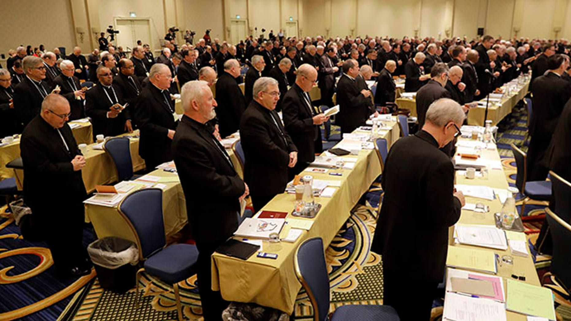 Members of the United States Conference of Catholic Bishops recite a group prayer during the USCCB's annual fall meeting in Baltimore, Tuesday, Nov. 15, 2016. Cardinal Daniel DiNardo of the Archdiocese of Galveston-Houston was elected Tuesday as president of the USCCB. (AP Photo/Patrick Semansky)