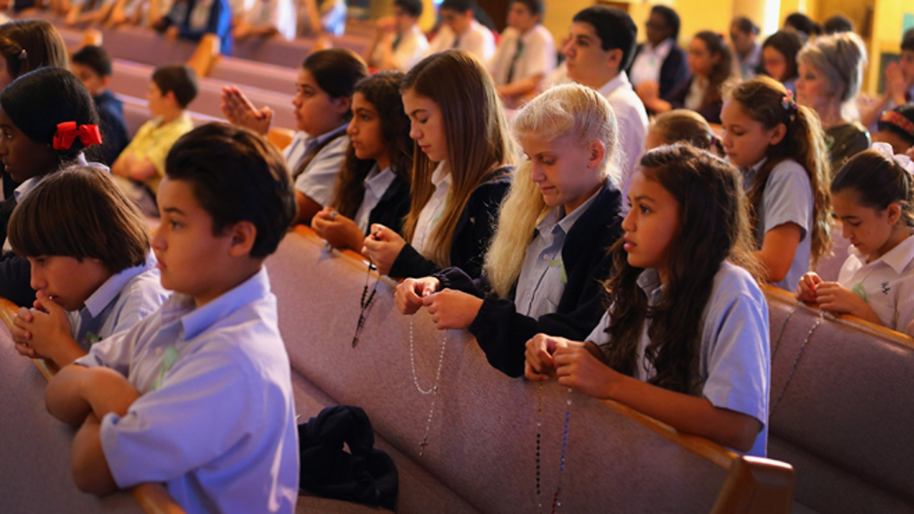 Children pray during a service, at St. Rose of Lima School on December 21, 2012 in Miami, Florida.