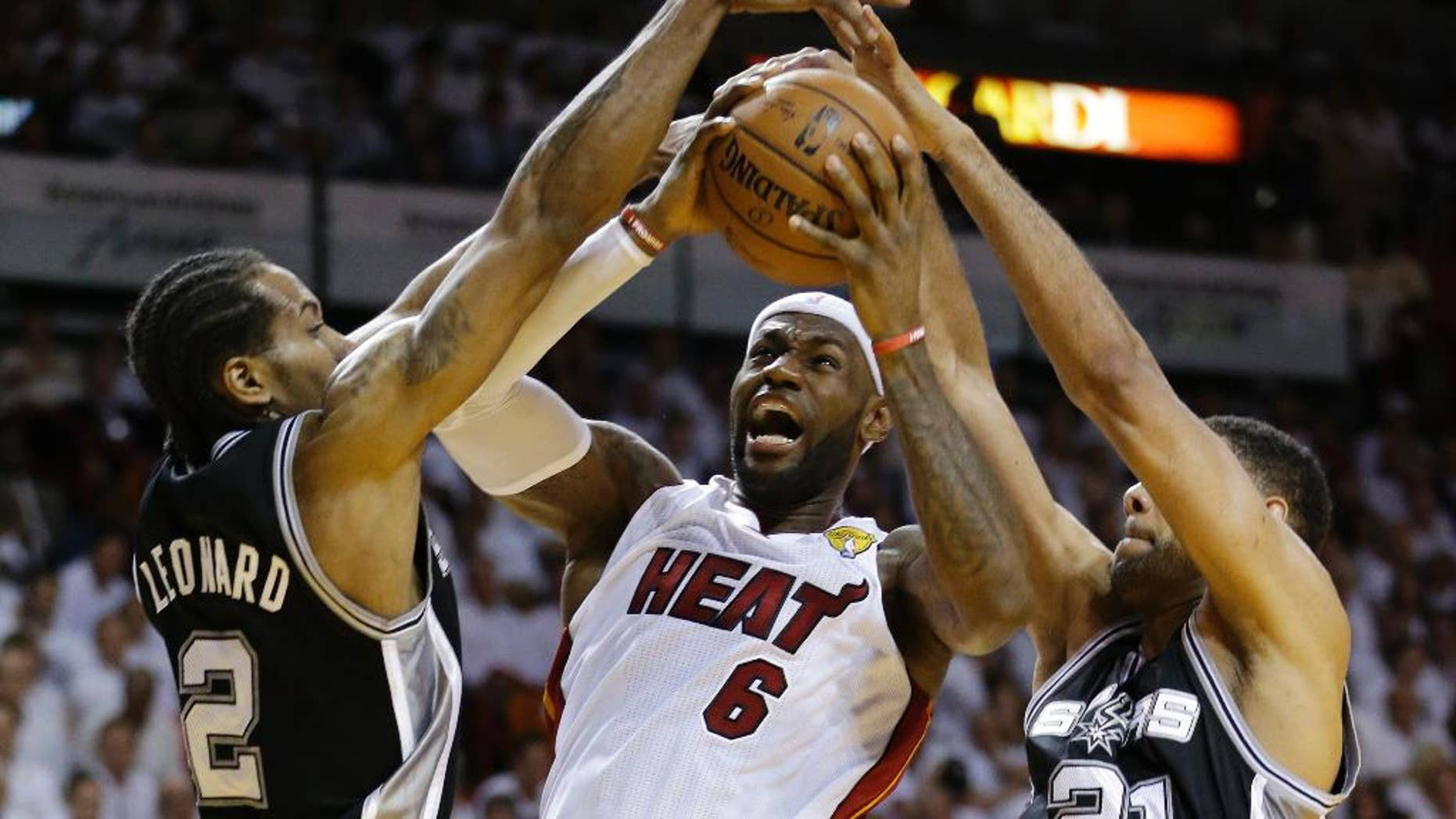 FILE - In this June 10, 2014, file photo, San Antonio Spurs forward Tim Duncan (21) and forward Kawhi Leonard (2) defend against Miami Heat forward LeBron James (6), during the first half in Game 3 of the NBA basketball finals in Miami. They've denied LeBron James winning two NBA titles, and in last year's Finals the Spurs dismantled the Heat, a beatdown that may have hastened the superstar's decision to re-sign with the Cavaliers. On Wednesday, Nov. 19, James faces his nemesis for the first time since June. By(AP Photo/Wilfredo Lee, File)