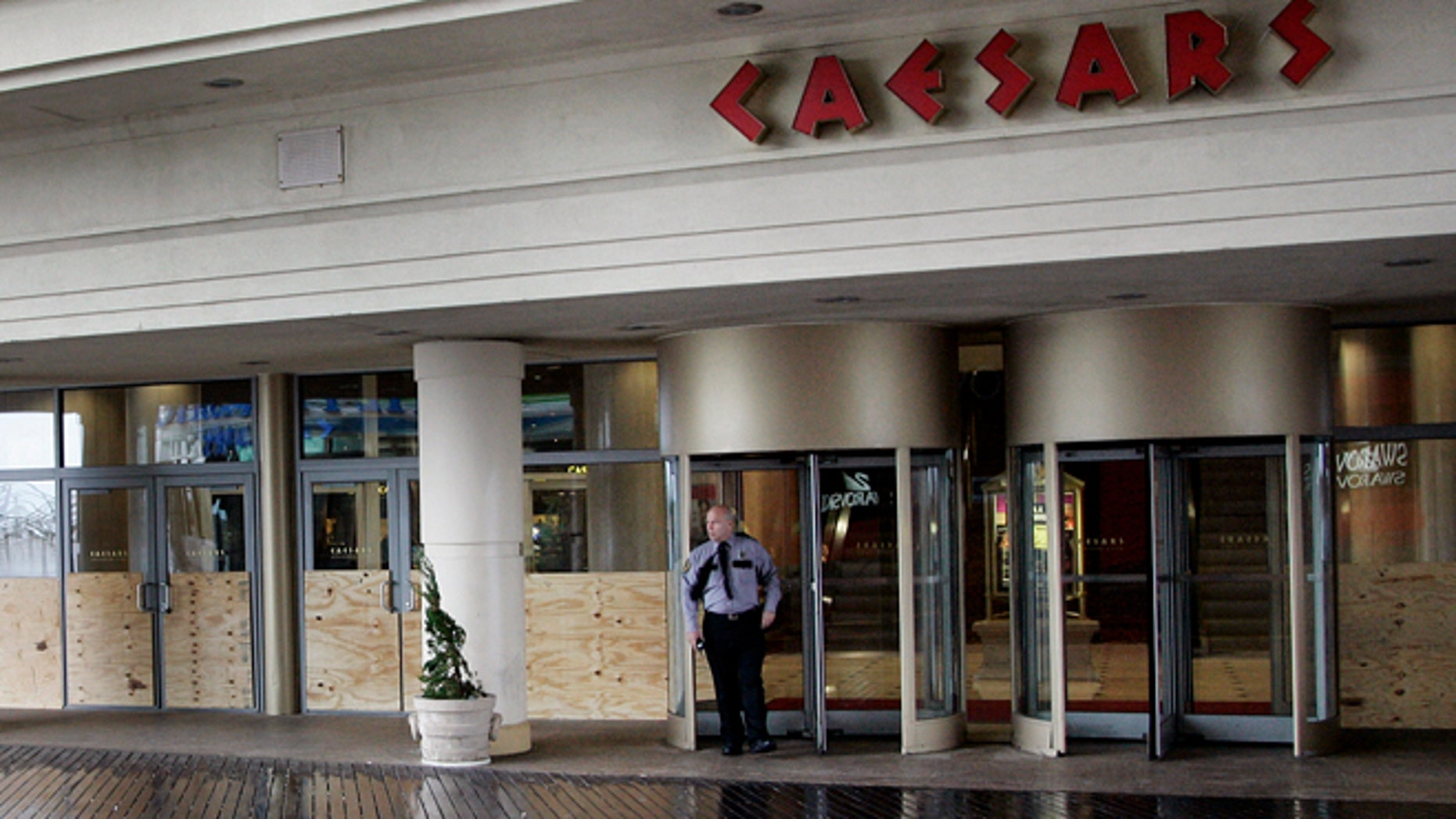 FILE: A security guard stands outside the entrance of Caesar's Casino on the Atlantic City boardwalk.