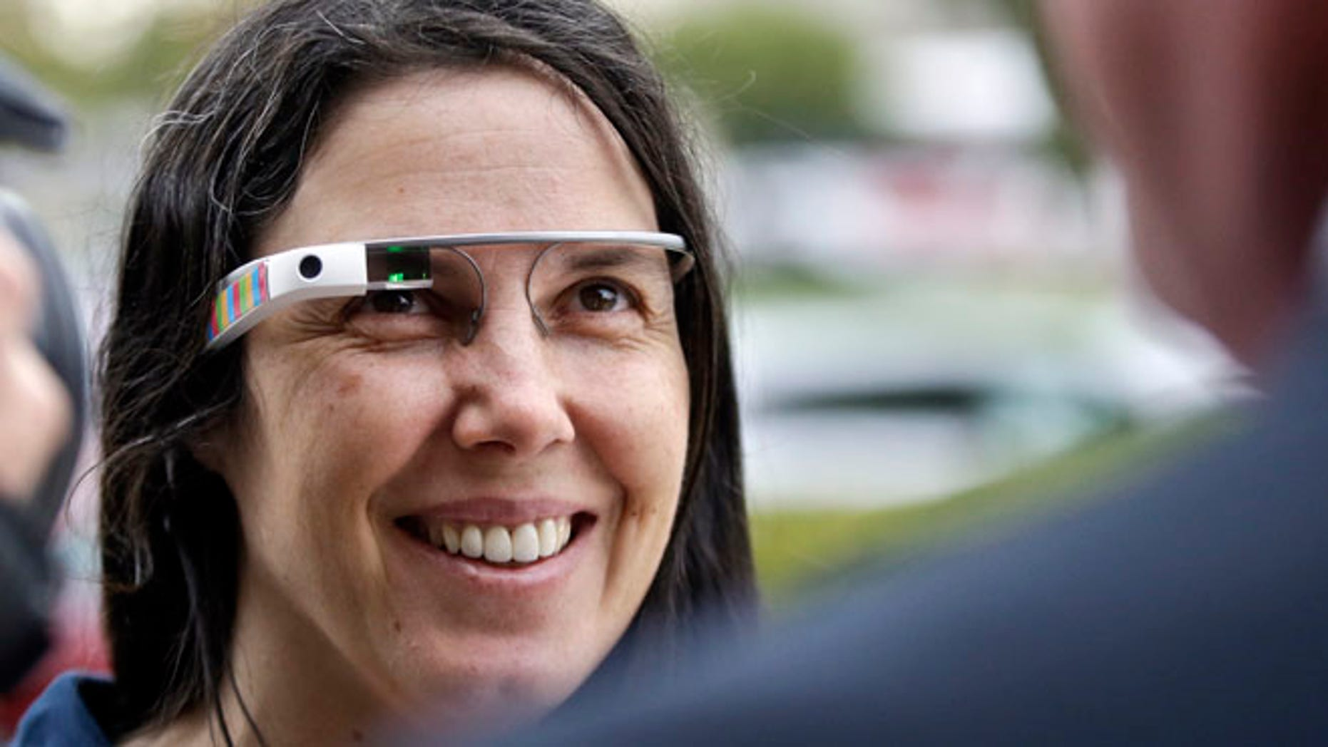 Cecilia Abadie wears her Google Glass as she talks with her attorney outside of traffic court in this Dec. 3, 2013 file photo taken in San Diego. The California woman believed to be the first cited for wearing Google's computer-in-an-eyeglass while driving says she was within her rights and violated no law. The case to be tried Thursday Jan. 16, 2014 in a San Diego traffic court could help shape future laws on wearable technology as it goes mainstream.