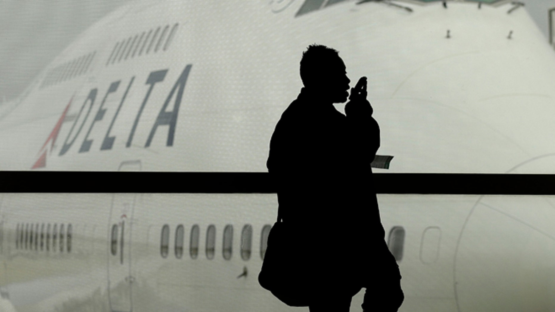 A traveler on Delta Airlines waits for her flight in Detroit. As federal regulators consider removing a decades-old prohibition on making phone calls on planes, a majority of air travelers oppose such a change, a recent poll found.